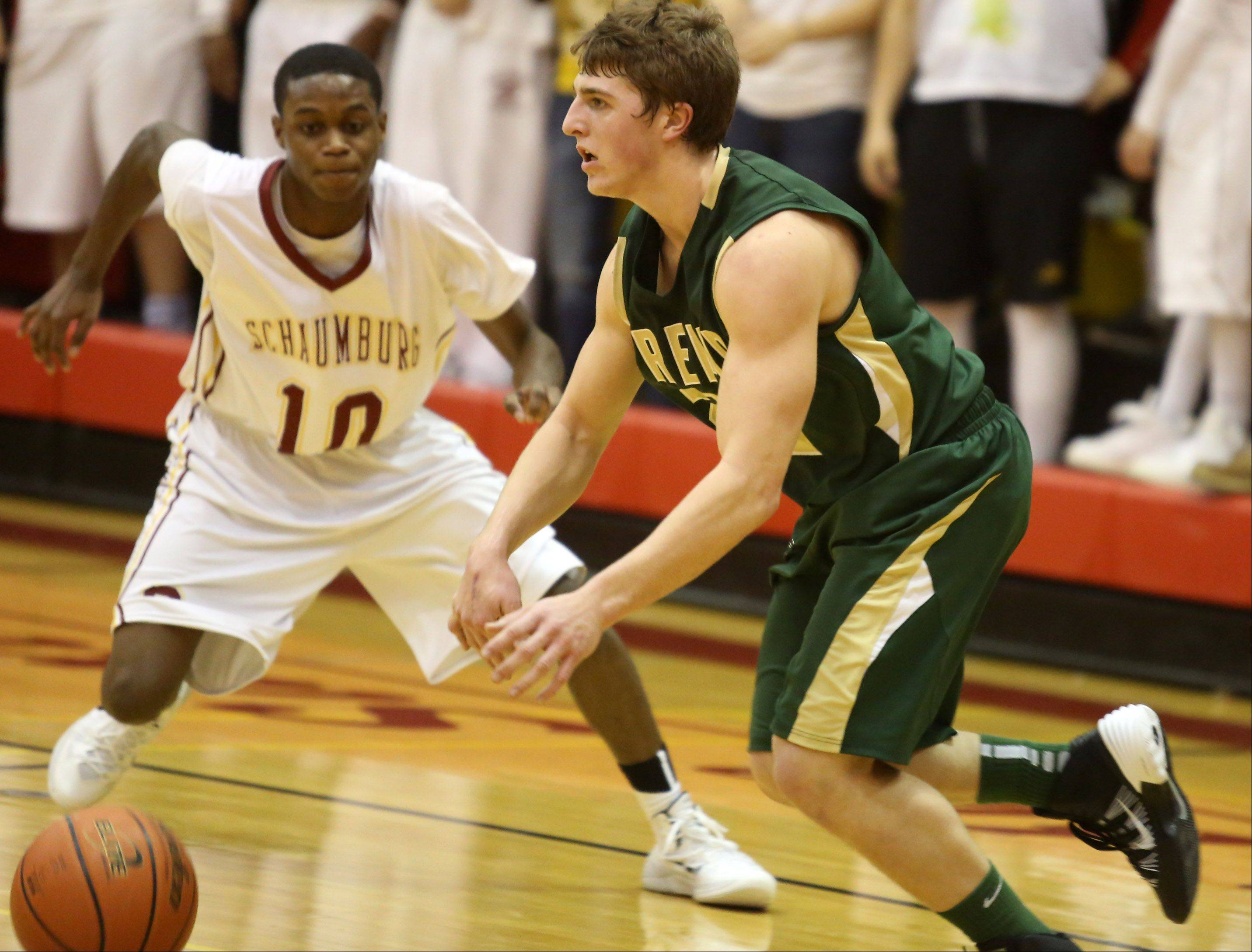 Fremd guard Garrett Groot pushes the ball up court against Schaumburg defender Marquis Woodard.