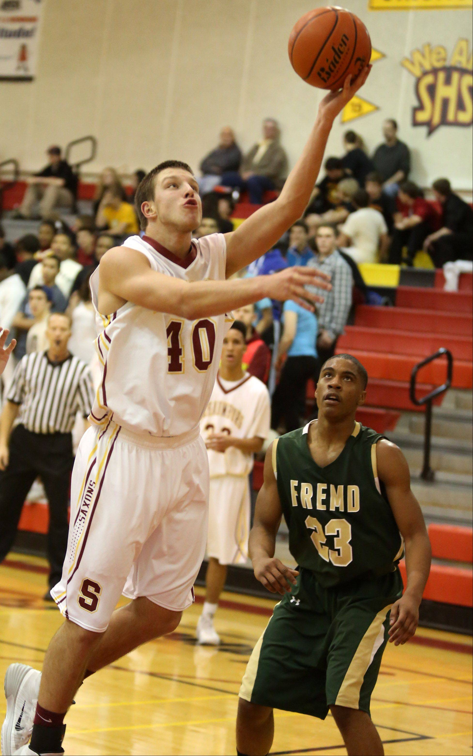 Schaumburg forward Joshua Rahn shoots over Fremd defender Xavier Williams.