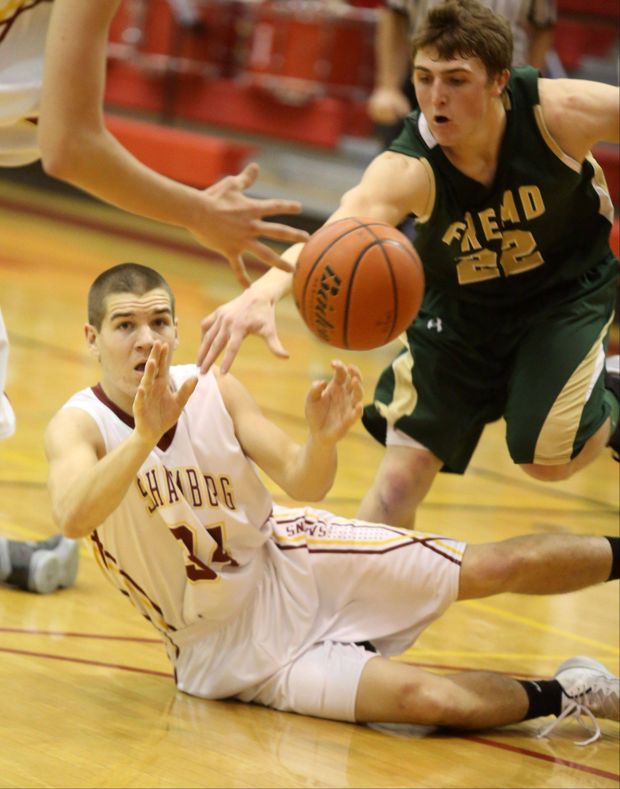 Schaumburg guard Christopher Mullaney passes the ball from the floor as Fremd defender Garrett Groot reaches for the ball.