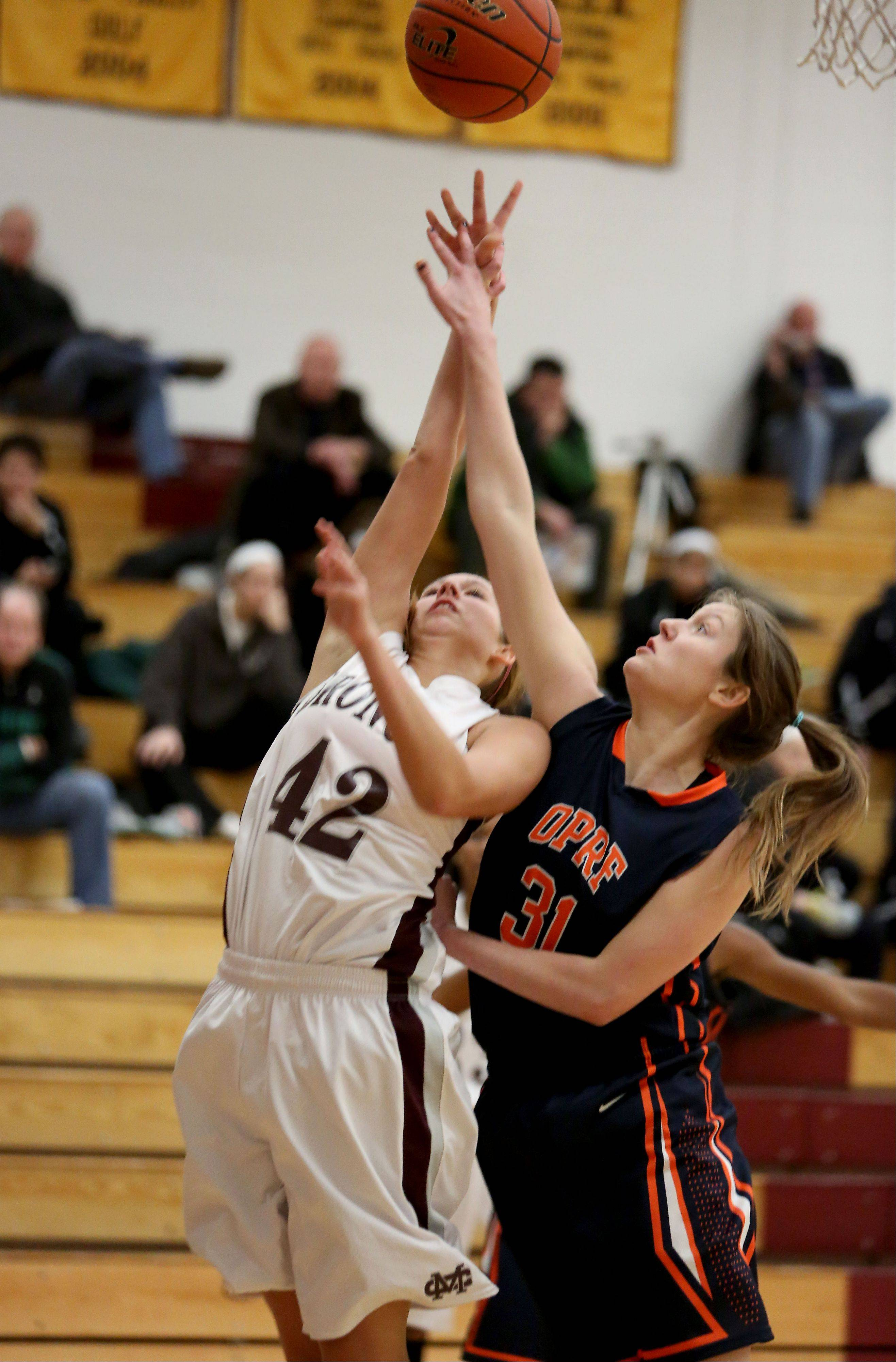 Calire Jakaitis, left of Montini and Gareth Coalson, right, of Oak Park River Forest, go for a rebound in the Montini Catholic High School Girls Basketball Christmas Tournament on Monday in Lombard.