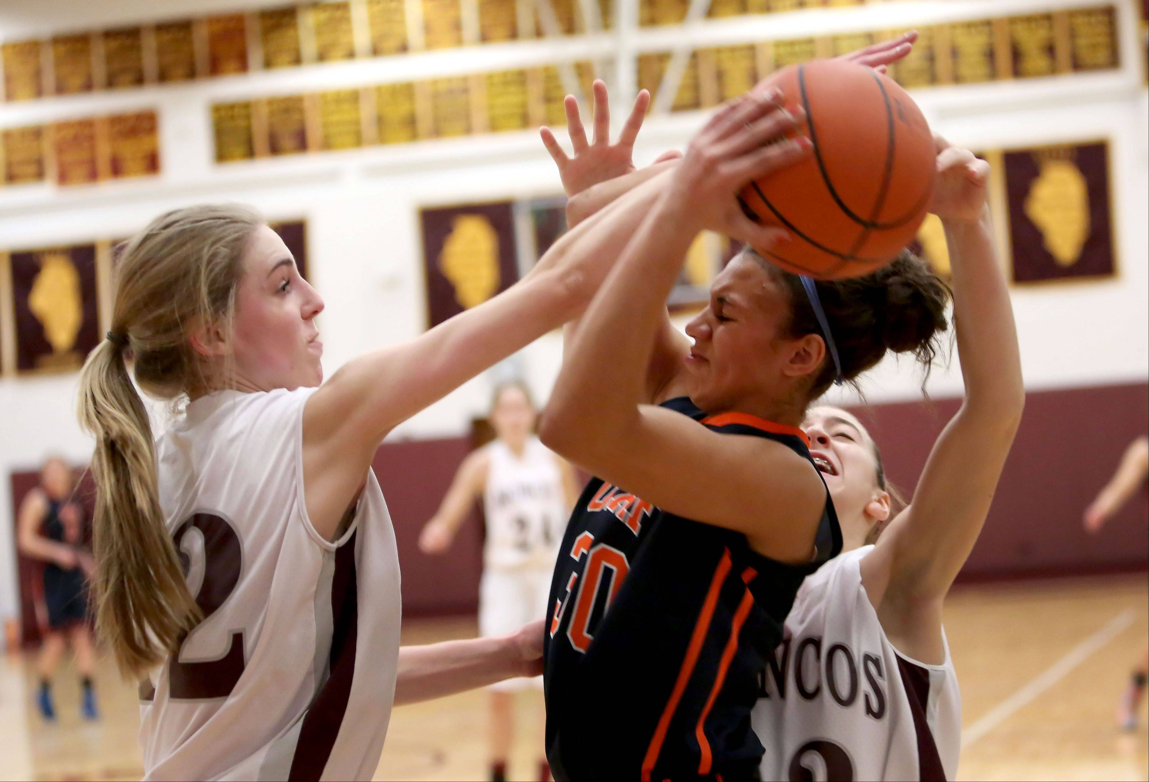 Kelly Karlis, left, and Claudia Kunzer, right, of Montini put the pressure on Chardonnay Harris of Oak Park River Forest in the Montini Catholic High School Girls Basketball Christmas Tournament on Monday in Lombard.