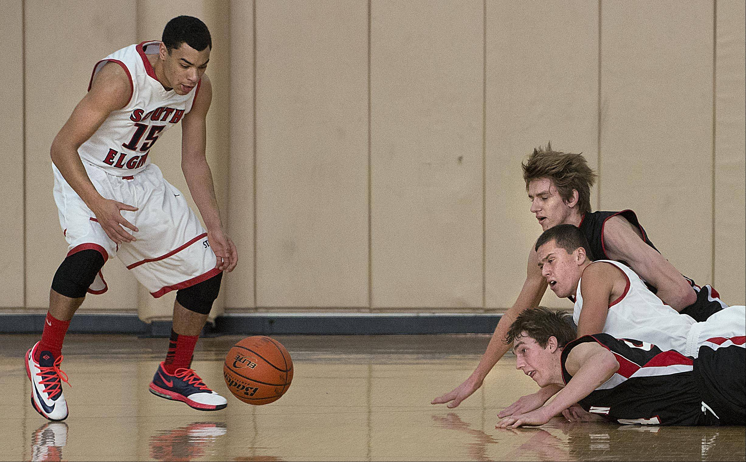 Barrington's Rapolas Ivanauskas and West McDonald and South Elgin's Matt McClure watch as South Elgin's Matthew Smith reaches for a loose ball Monday at the Hinkle Holiday Classic at Jacobs High School in Algonquin.