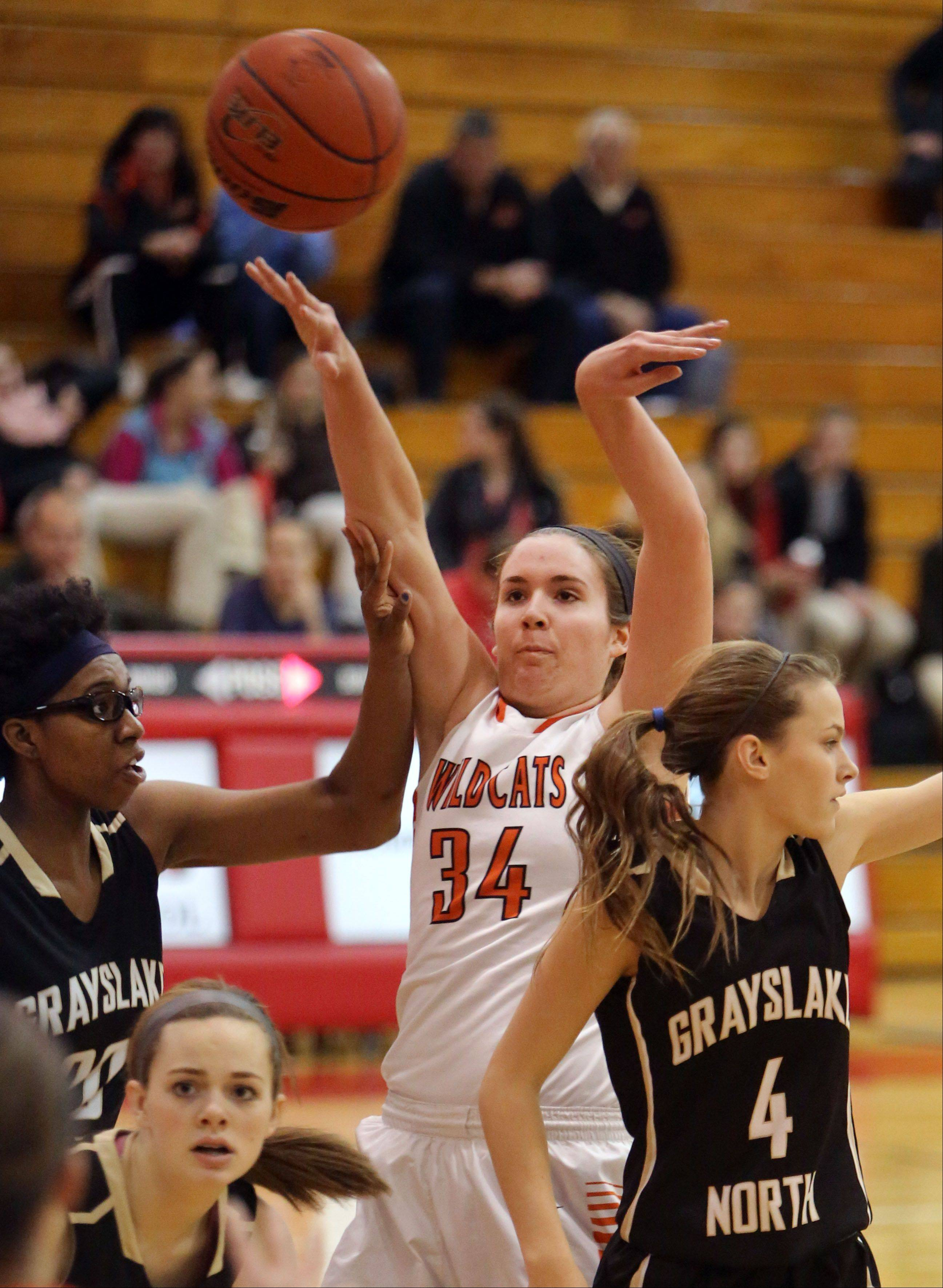 Libertyville's Becky Deichl passes over Grayslake North's Brittany Thibeaux, left, and Maggie Fish on Thursday at Mundelein.