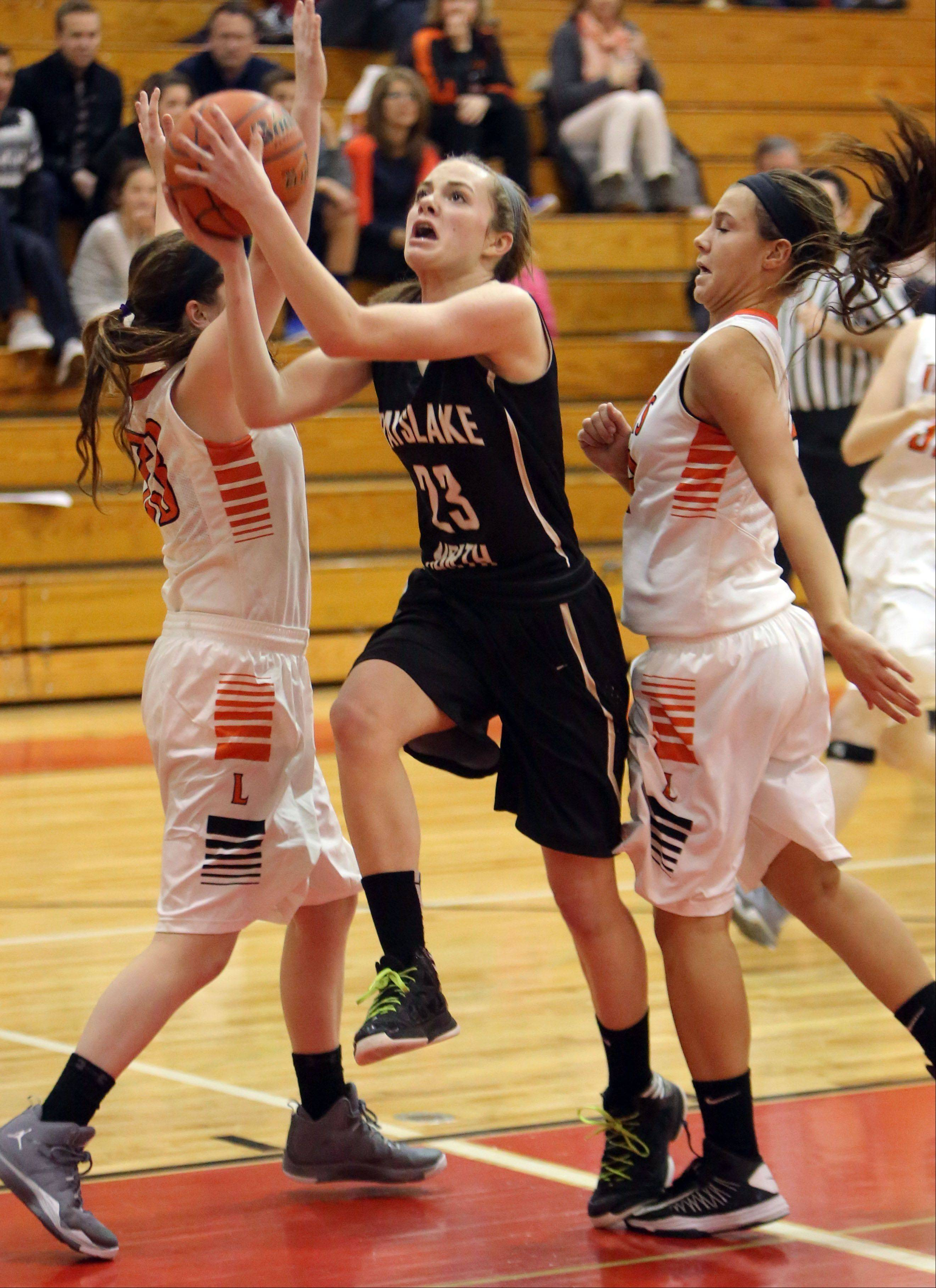 Grayslake North's Sydney Lovitsch drives through Libertyville's Sydney Mudd, left, and Mary Wilterdink on Thursday at Mundelein.