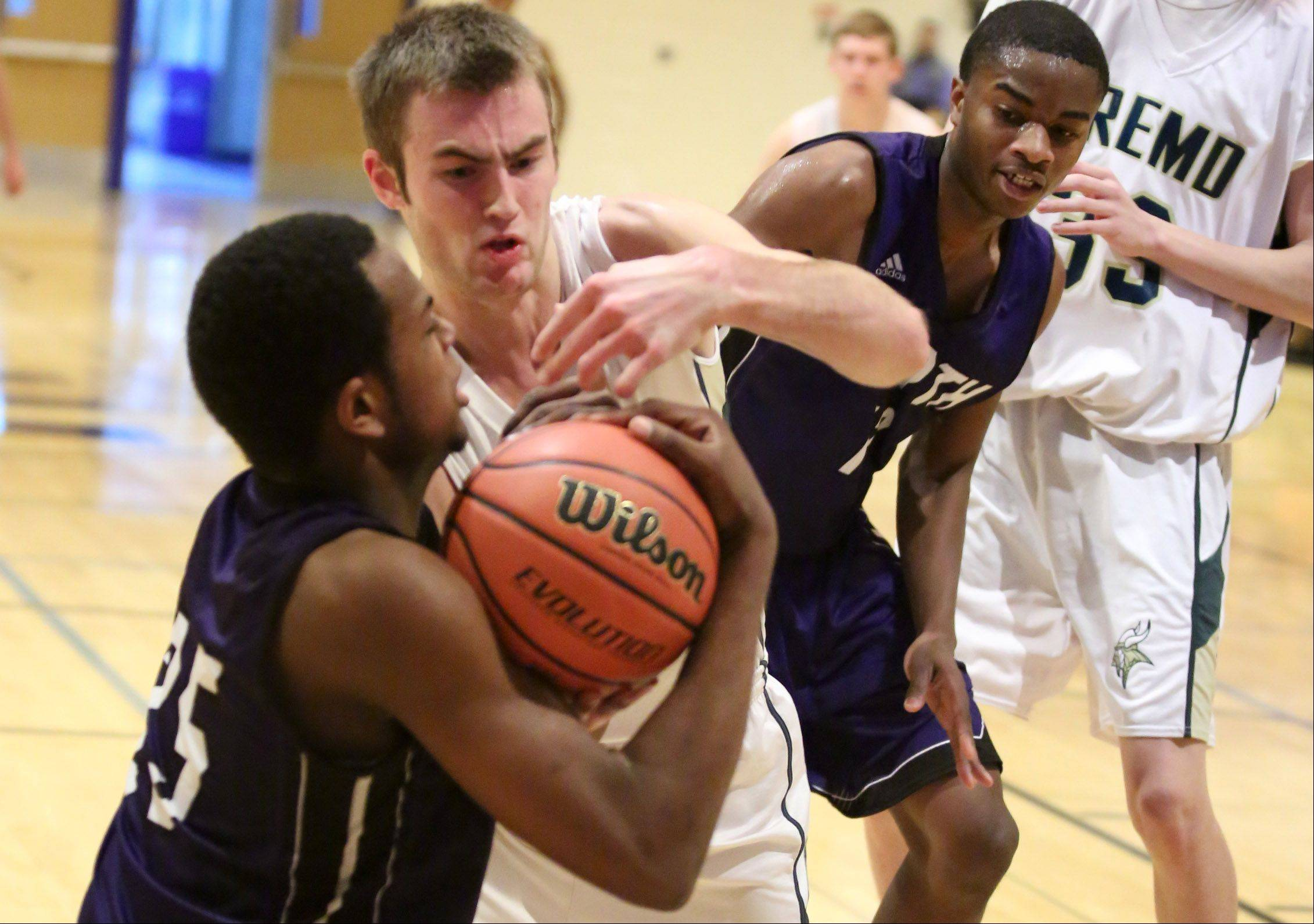 Fremd guard Riley Glassmann, center, fights for the ball against Niles North guard Danillo Ranger on Thursday at the Wheeling Hardwood Classic.