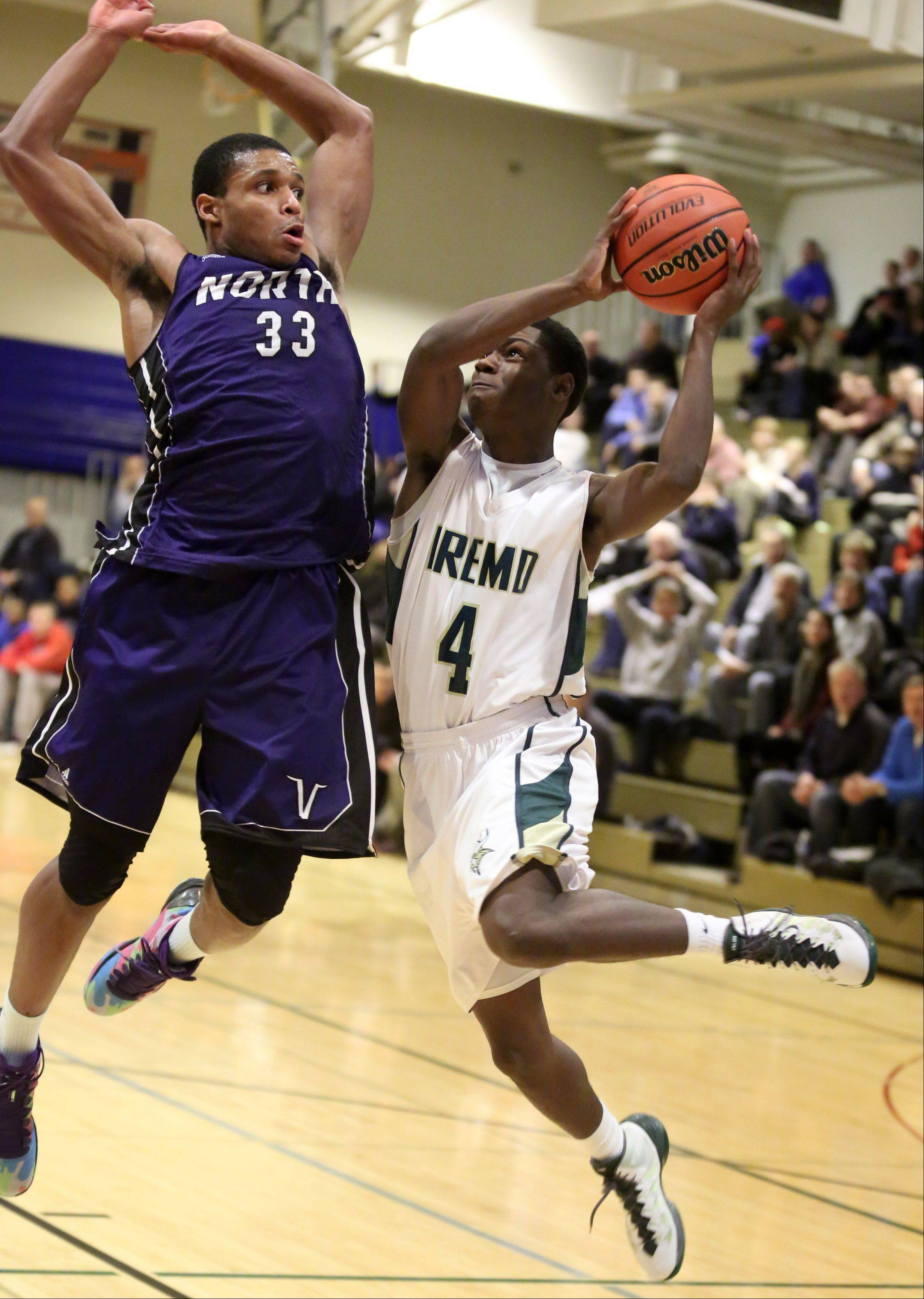 Fremd guard Jalon Roundy drives and shoot from under the basket against Niles North defender Duante Stephens on Thursday at the Wheeling Hardwood Classic.