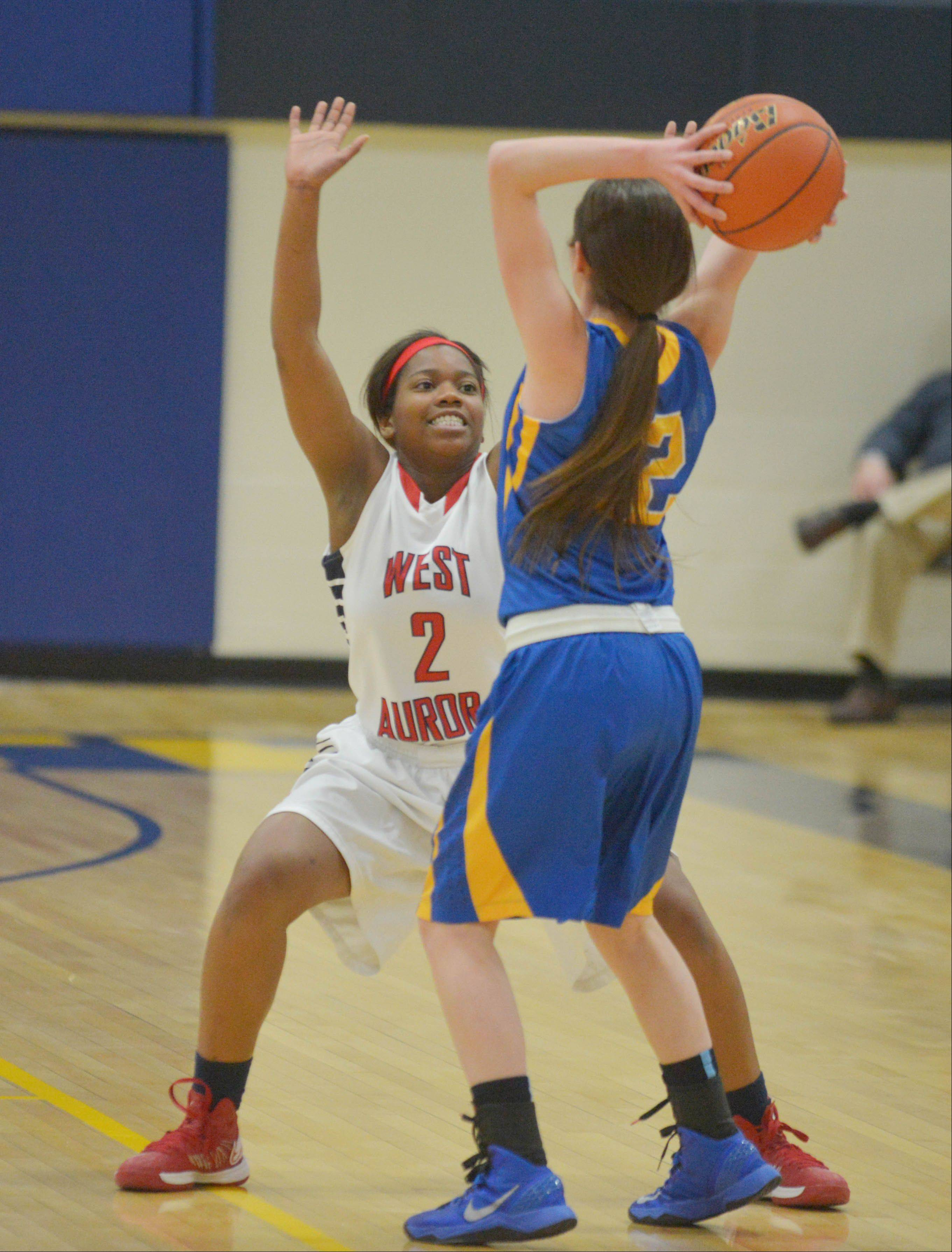 Ashley Williams of West Aurora attempts to block Nina Scaramella of Lyons during the West Aurora at Wheaton North girls basketball tournament game Thursday.