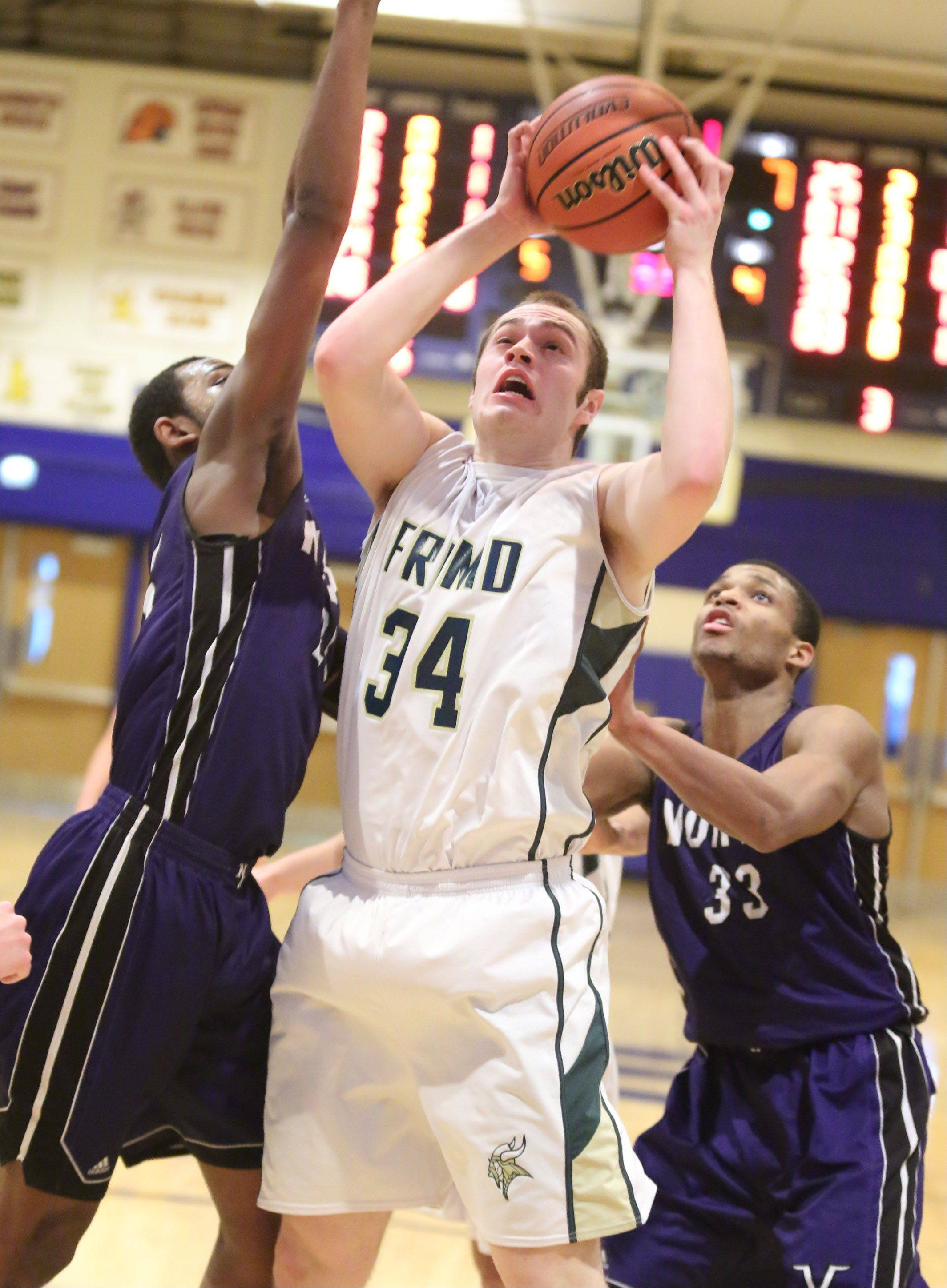 Fremd forward Benjamin Carlson pulls down an offensive rebound and shoots while splitting two Niles North defenders including Duante Stephens, right, on Thursday at the Wheeling Hardwood Classic.
