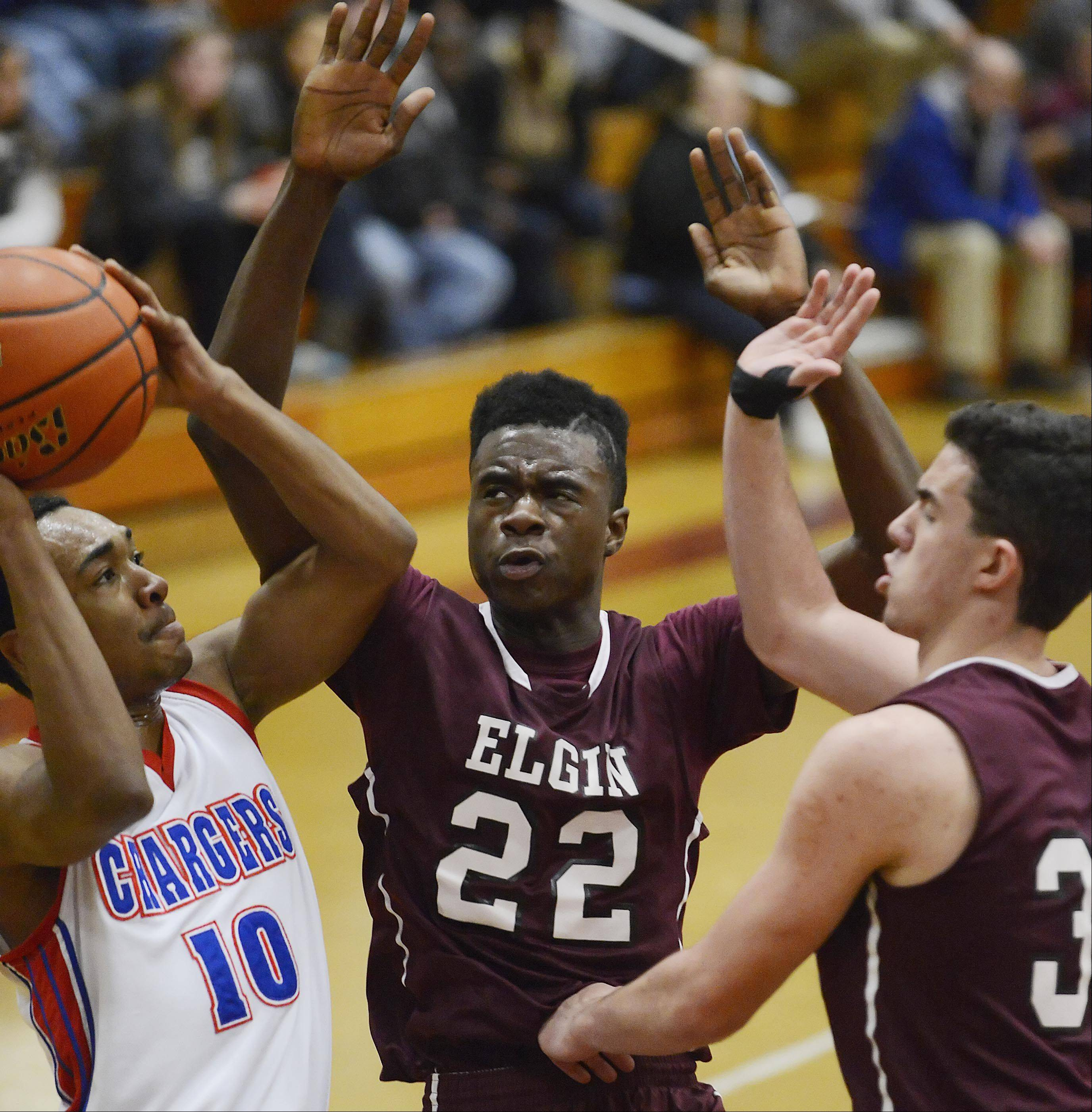 Elgin's Desmond Sanders and Mike Hanneman defend Dundee-Crown's Kiwaun Seals Thursday in the quarterfinal game of the Elgin Holiday Tournament.