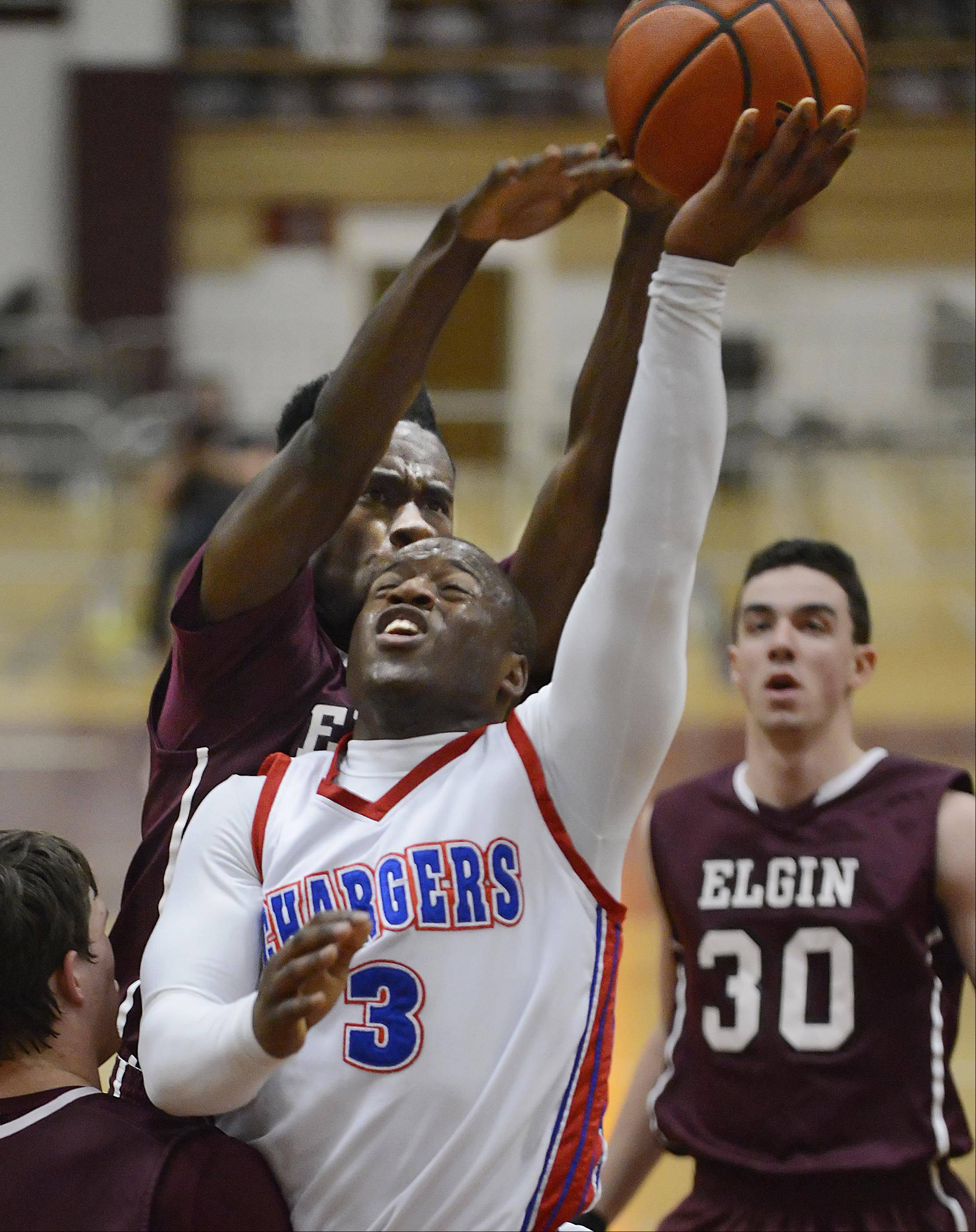 Elgin's Desmond Sanders fouls Dundee-Crown's Cordero Parson as he blocks his shot Thursday in the quarterfinal game of the Elgin Holiday Tournament.
