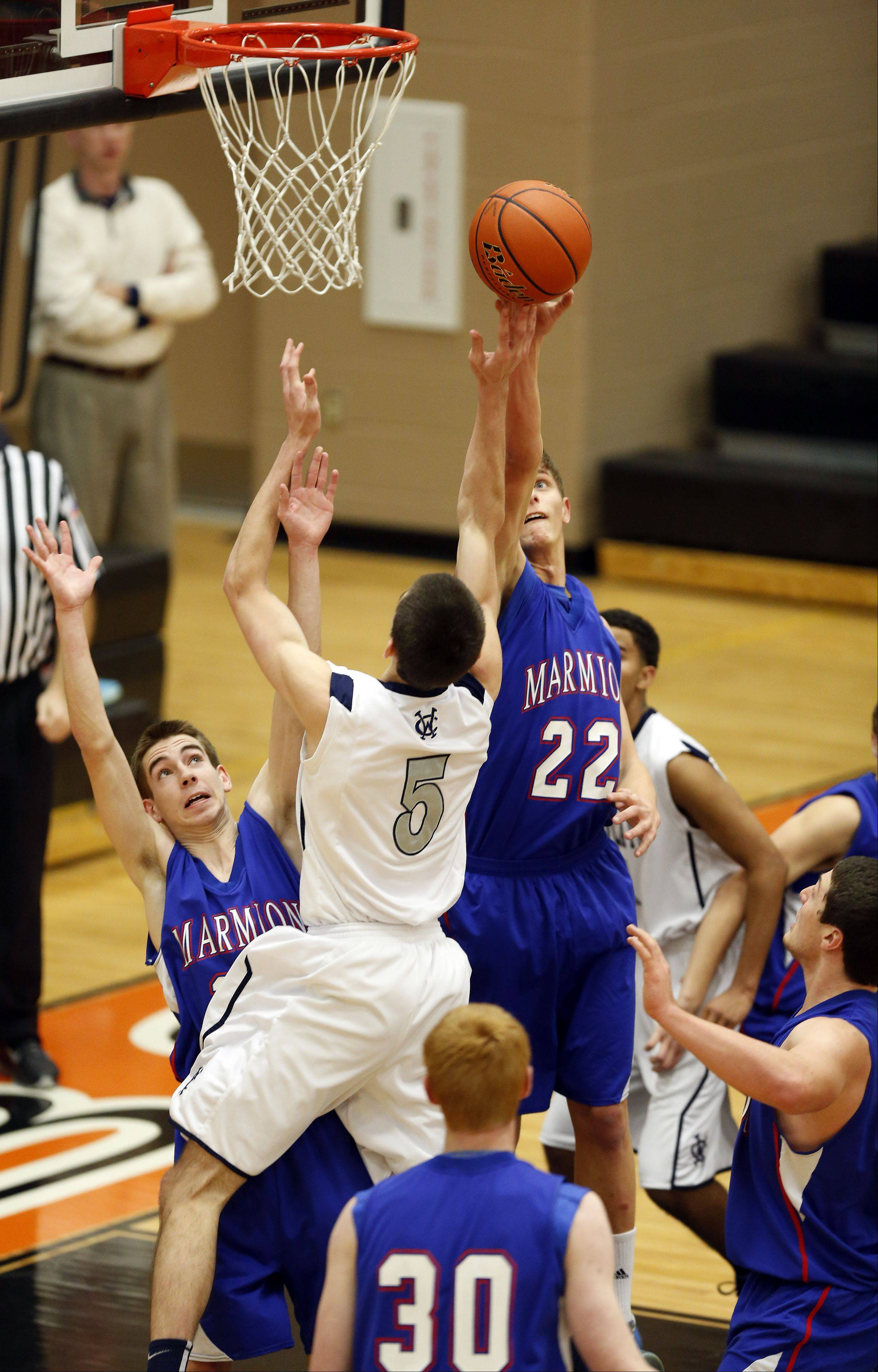 Marmion's Jake Esp, 22, knocks a shot away from West Chicago's John Konchar, 5, during the third place game at the 86th Annual Chuck Dayton Holiday Basketball Tournament at Dekalb High School Friday December 27, 2013.