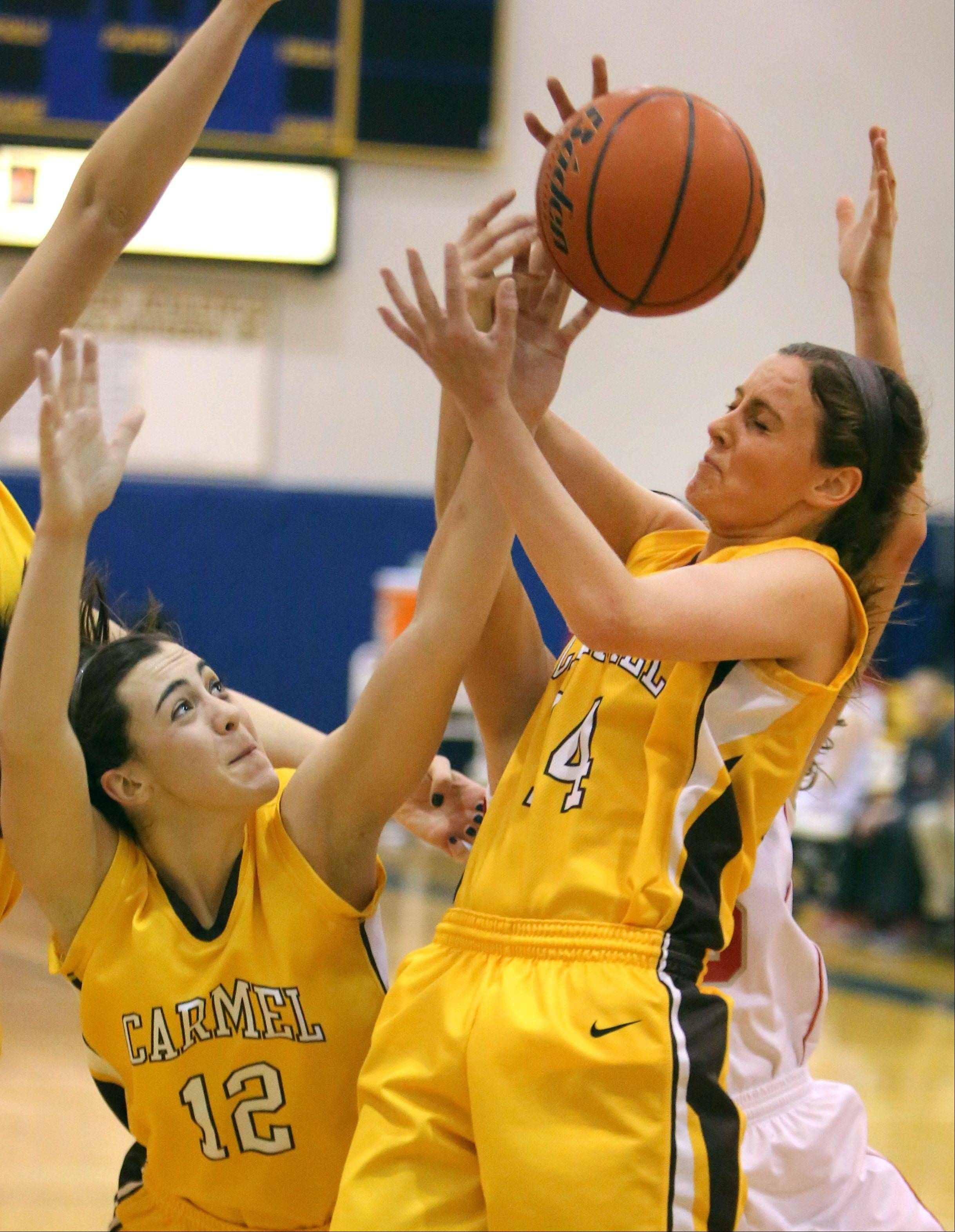 Carmel's Kathleen Felicelli, left and Casidy Kloss battle for a rebound against Palatine on Friday at Warren.