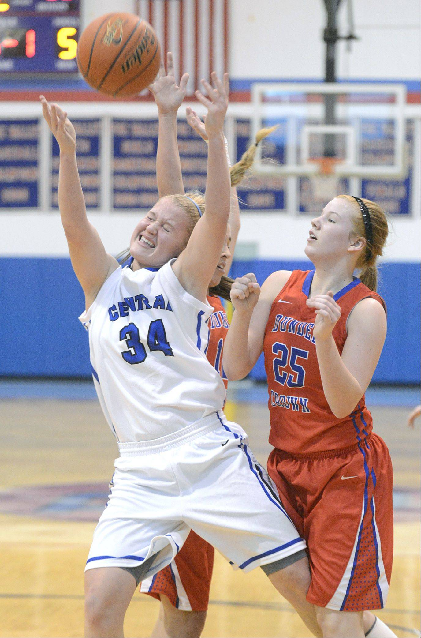 Burlington Central's Sam Pryor is fouled by Dundee-Crown's Lauren Lococo (behind) as she goes up for the hoop in the second quarter on Friday, December 27. Dundee-Crown's Allison Michalski on right.