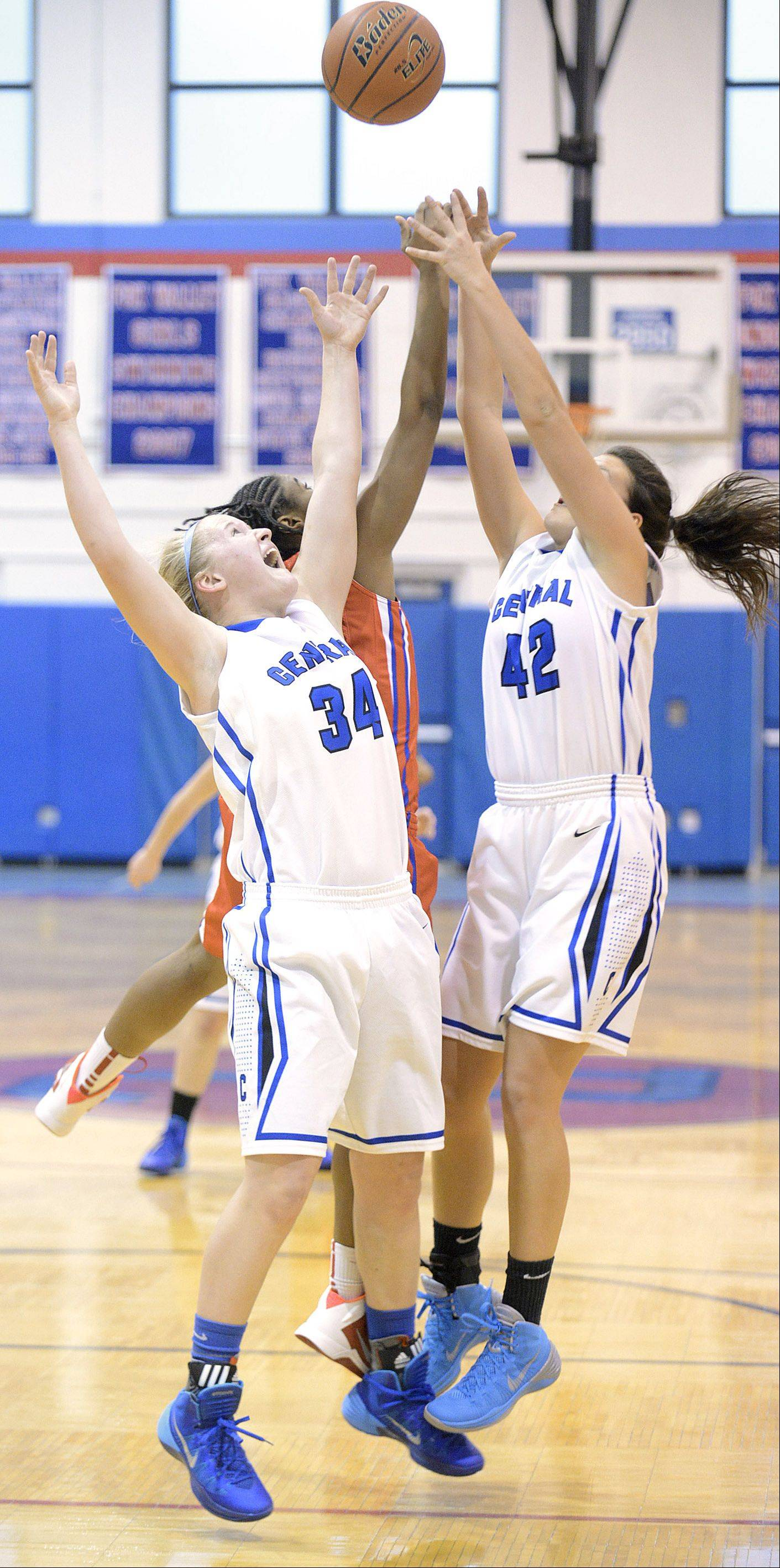Burlington Central's Sam Pryor (34) and Alison Colby (42) leap for a rebound with Dundee-Crown's Jerreneka Baker in the second quarter on Friday, December 27.
