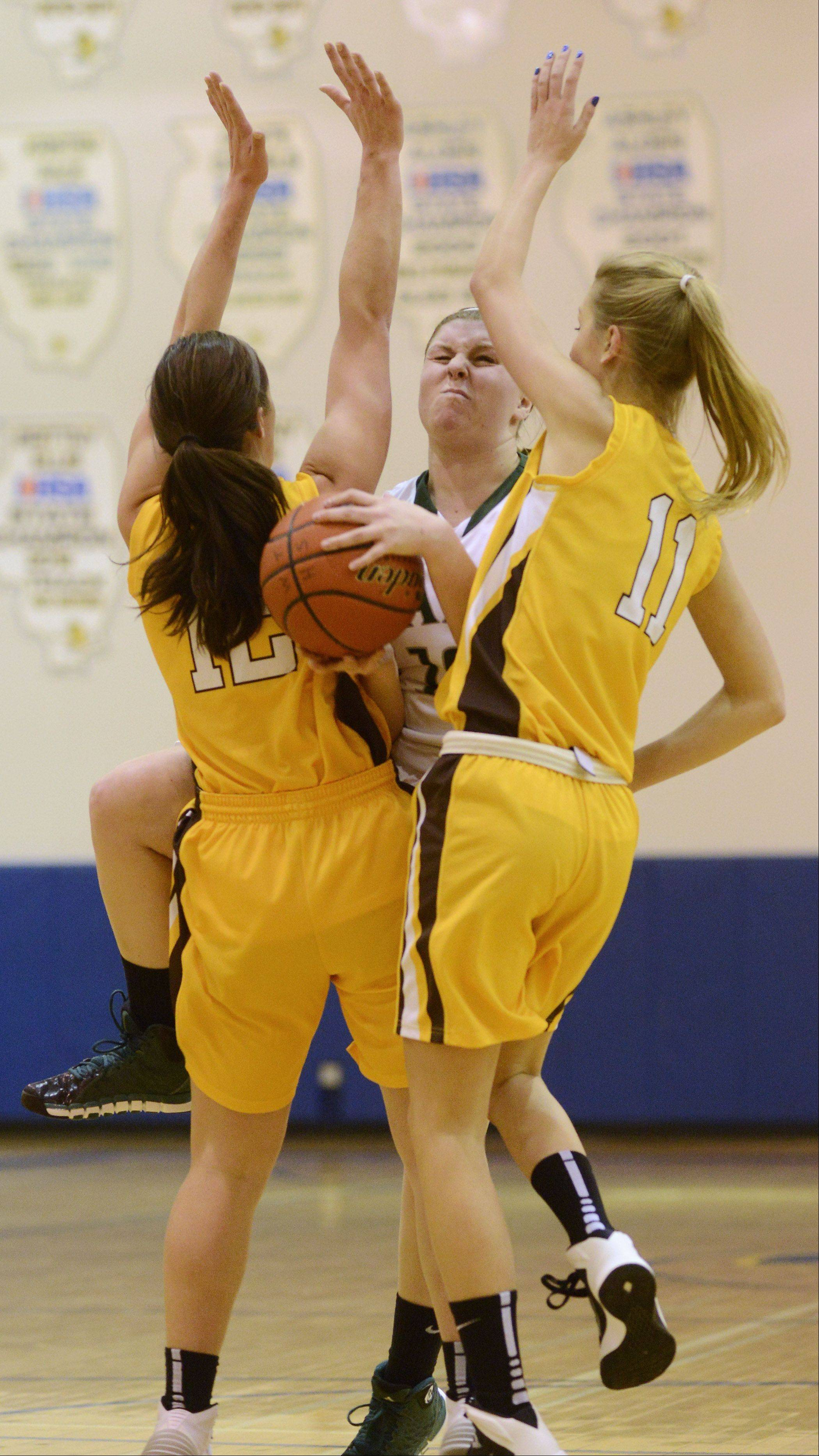 Carmel's Kathleen Felicelli, left, and Leah Leach, right, close in on Grayslake Central's Maddy Miller during Saturday's game at Warren.