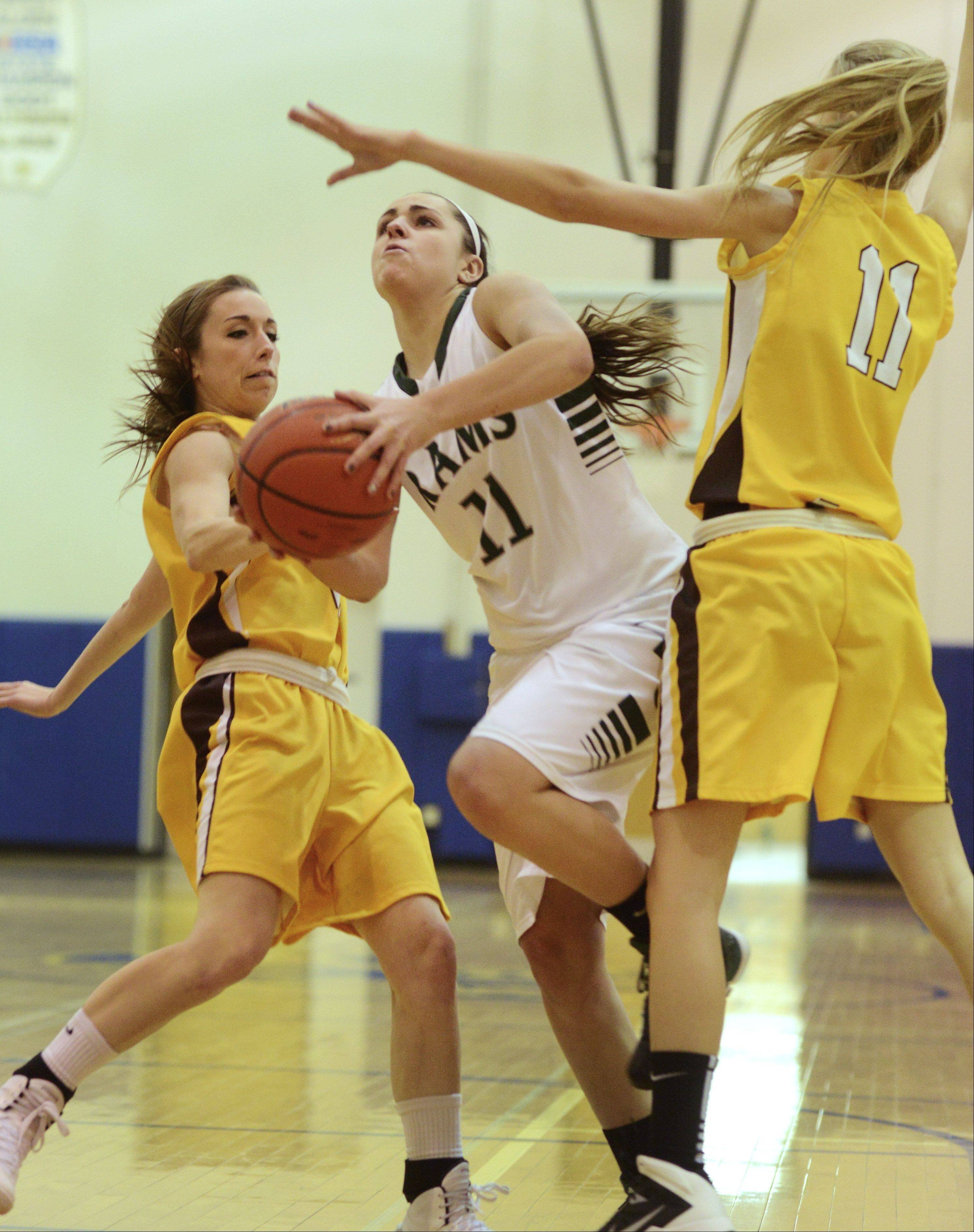 Grayslake Central's Carson Sparkman looks steps between Carmel's Nicole Bitter, left, and Leah Lach during Saturday's game at Warren.