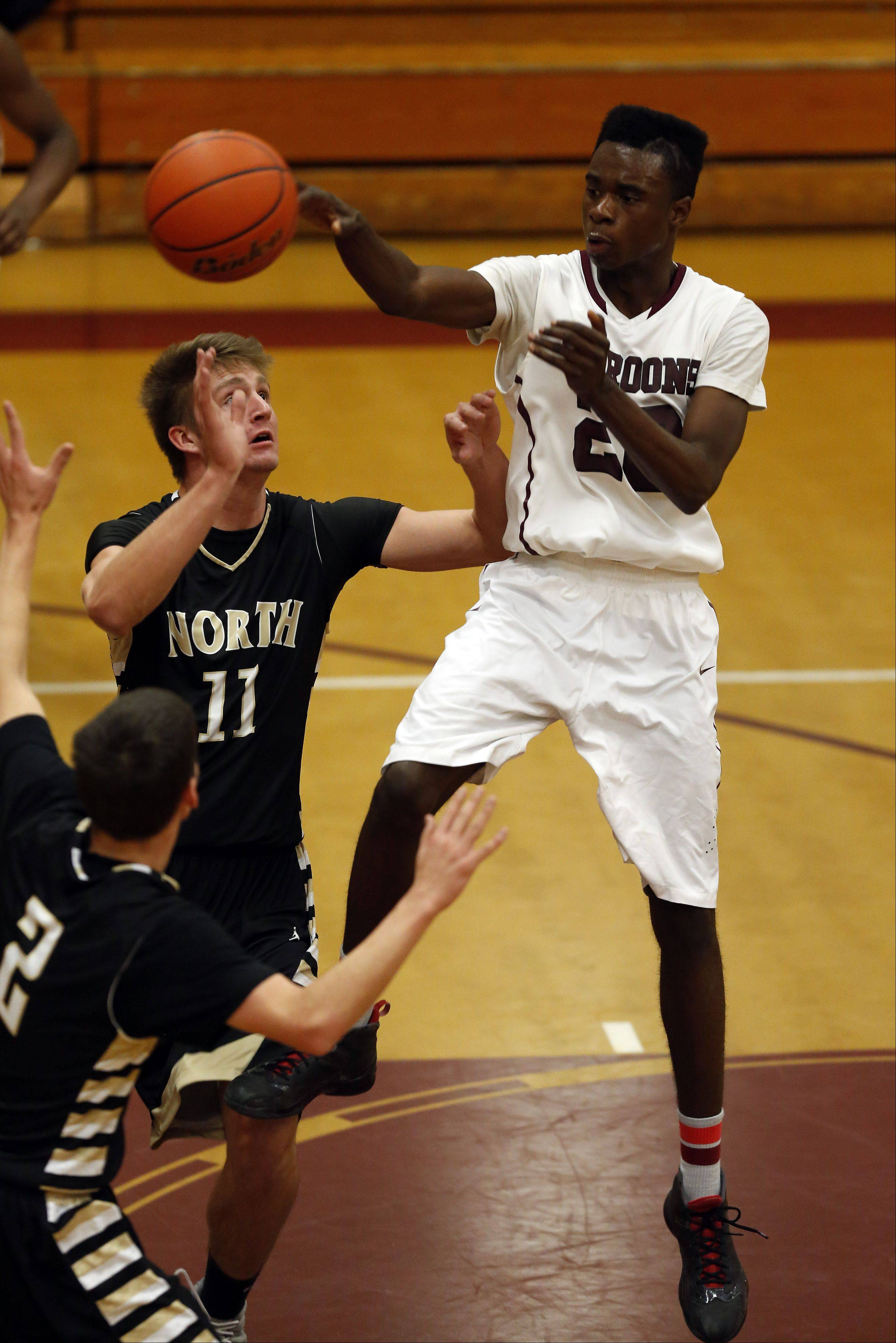 Elgin's Desmond Sanders, looks over Glenbard North's Brett Gasiorowski at the 39th Annual Elgin Boys Holiday Basketball Tournament at Elgin High School Saturday December 28, 2013.