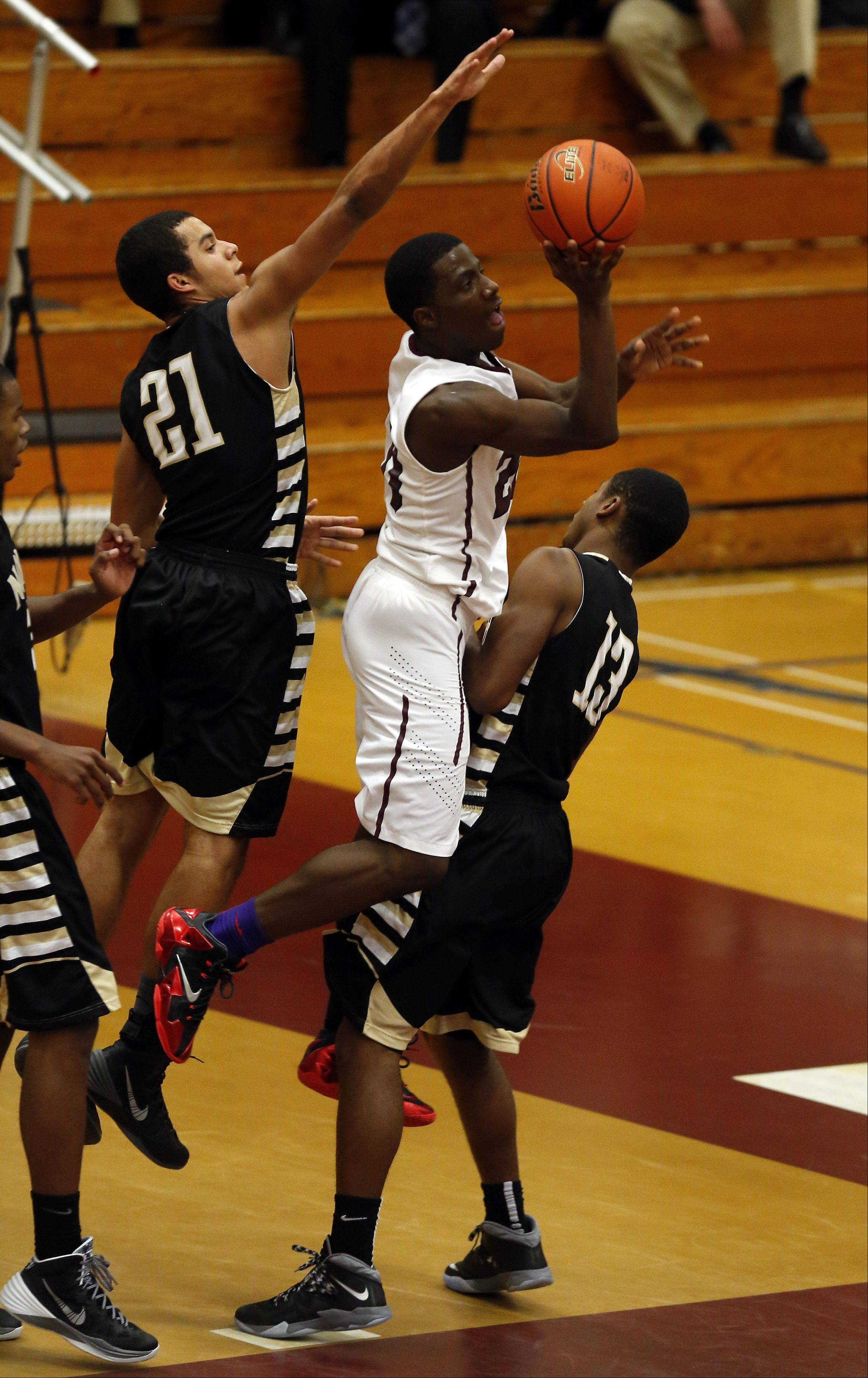 Elgin's Isaiah Butler goes strong to the hoop against Glenbard North's Kendall Holbert, left, and Justing Jackson, right, at the 39th Annual Elgin Boys Holiday Basketball Tournament at Elgin High School Saturday December 28, 2013.