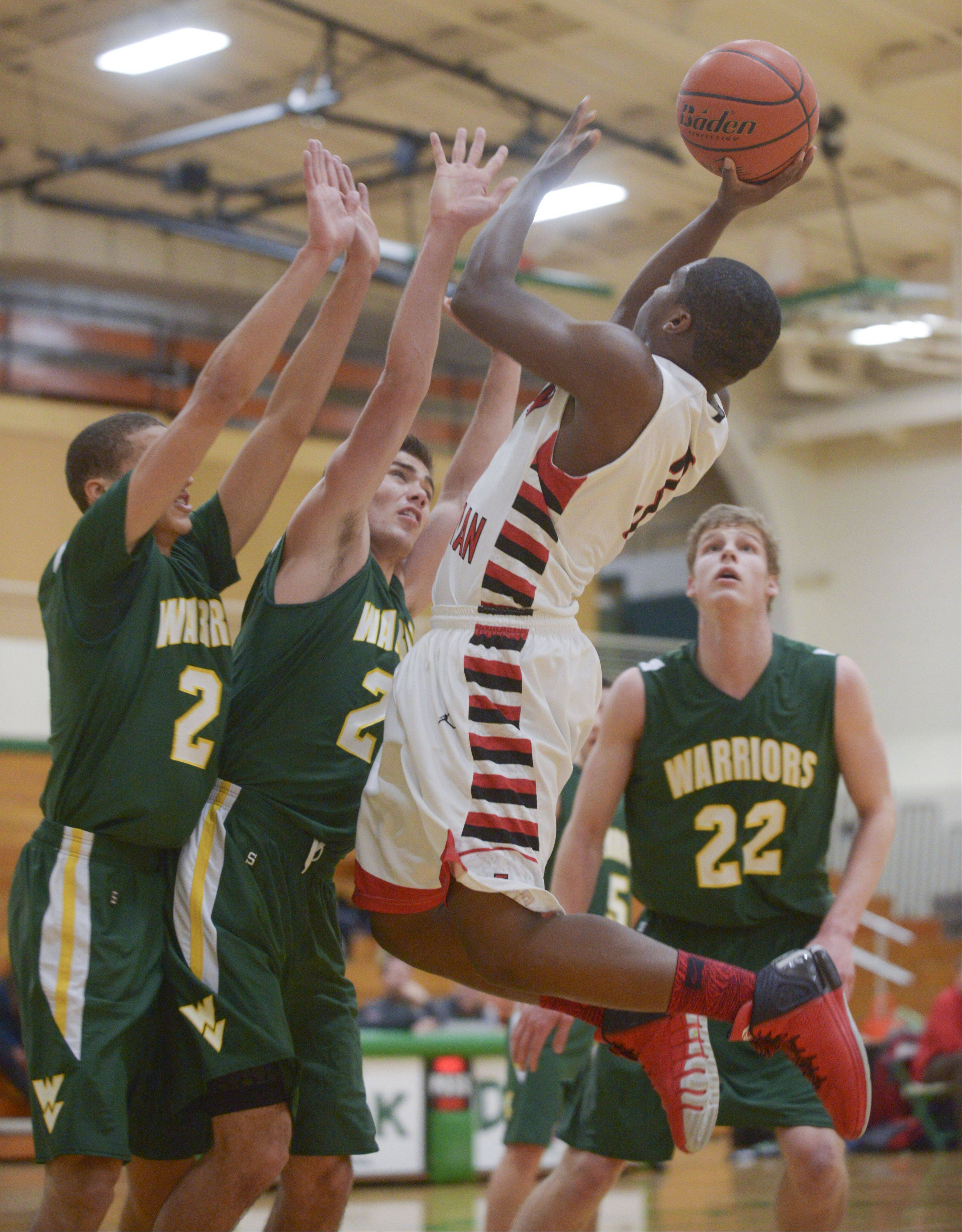 Timothy Christian's Malik Hughes takes a shot over Waubonsie Valley defenders during the Jack Tosh Holiday Classic at York High School Monday.