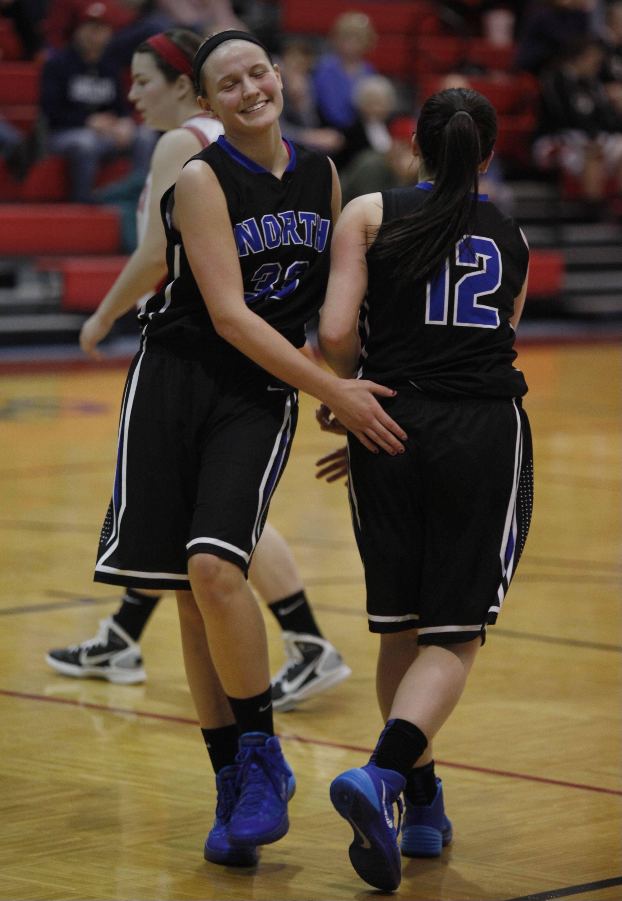 St. Charles North forward Nichole Davidson encourages her teammate, guard Sam Henry (12) after Henry took a hard foul while driving to the basket on the previous play Monday during the Dundee-Crown Charger Classic girls basketball tournament.