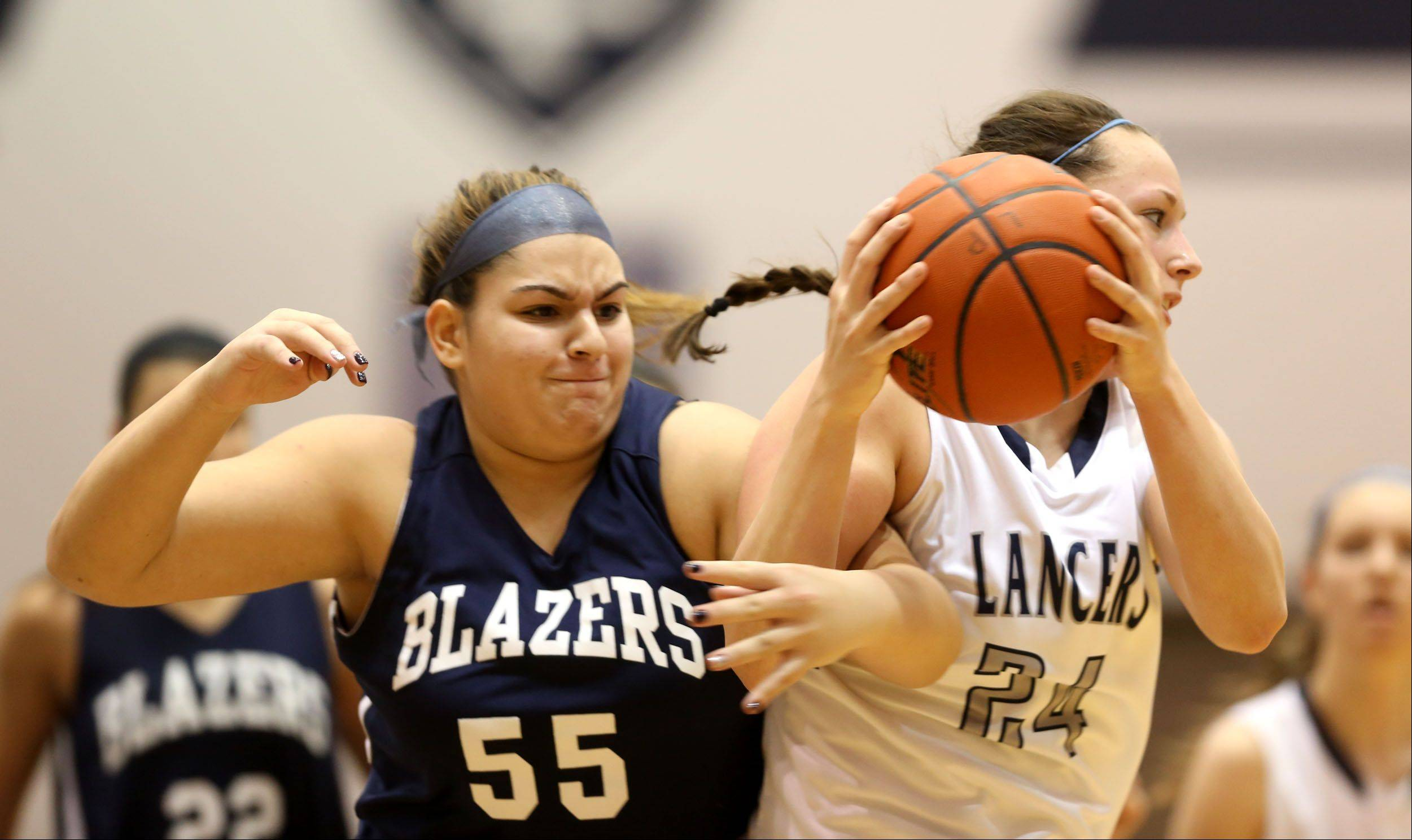 Addison Trail's Alexandar DIsilvio, left, battles Lake Park's Jen Warfield, right, during girls basketball action in Roselle.
