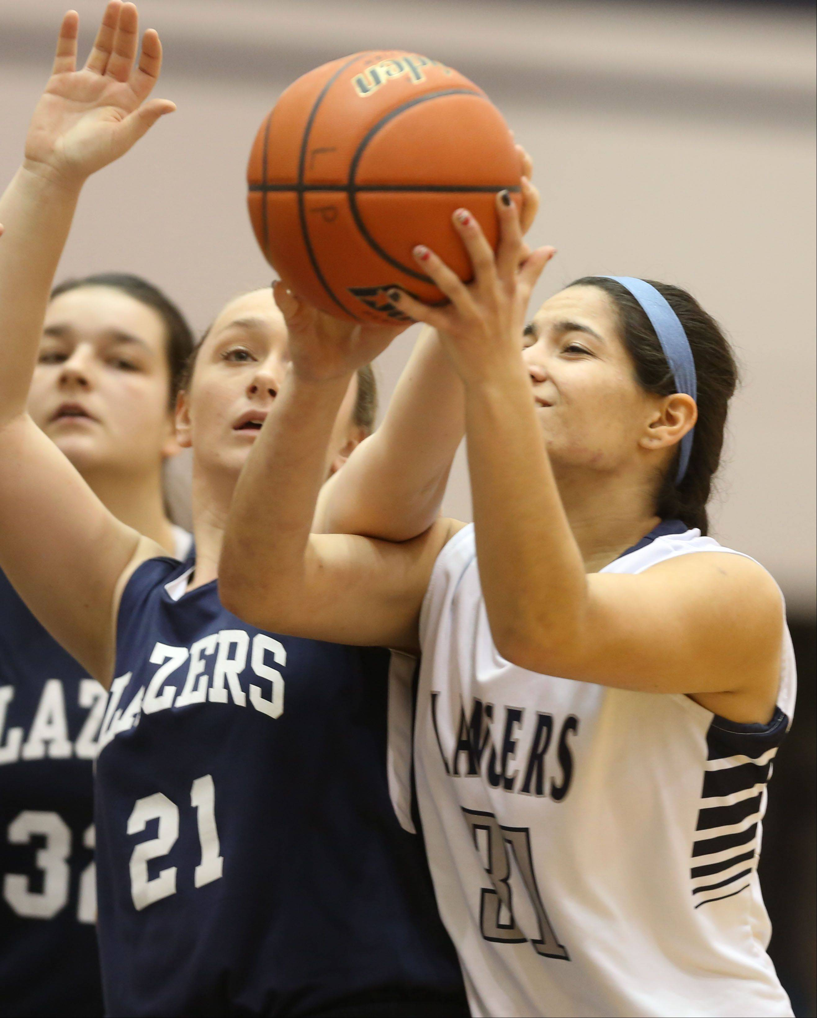 Addison Trail's Kelly Delawder, left, battles Lake Park's Lexie Ricchio, right, during girls basketball action in Roselle.