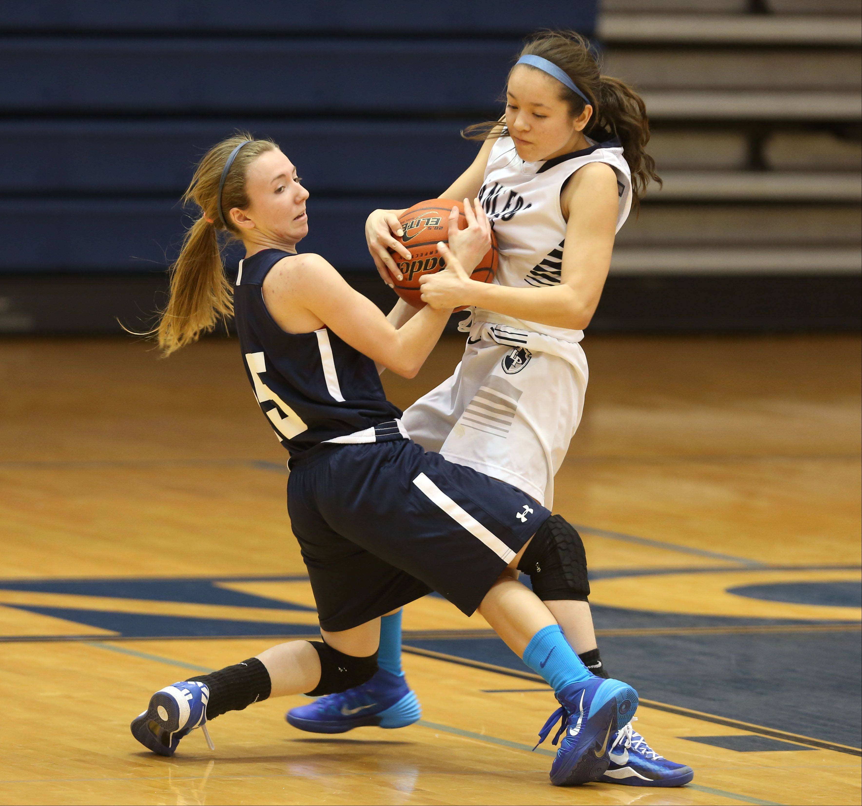 Addison Trail's Connie Barkoulies, left, battles Lake Park's Kelly Adams, right, during girls basketball action in Roselle.