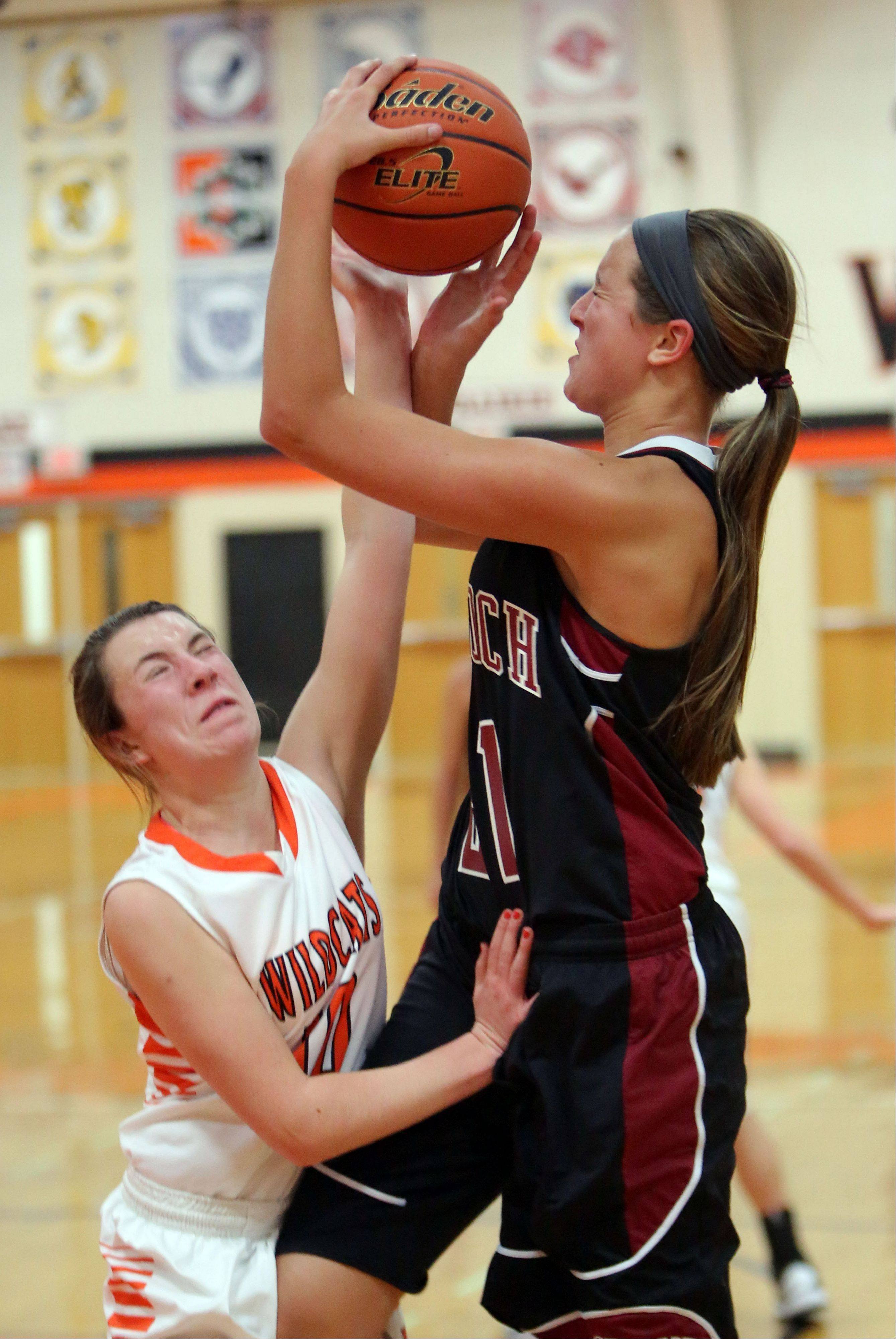 Antioch's Carly McCameron, right, drives to the hoop on Libertyville's Maggie Piazzi.