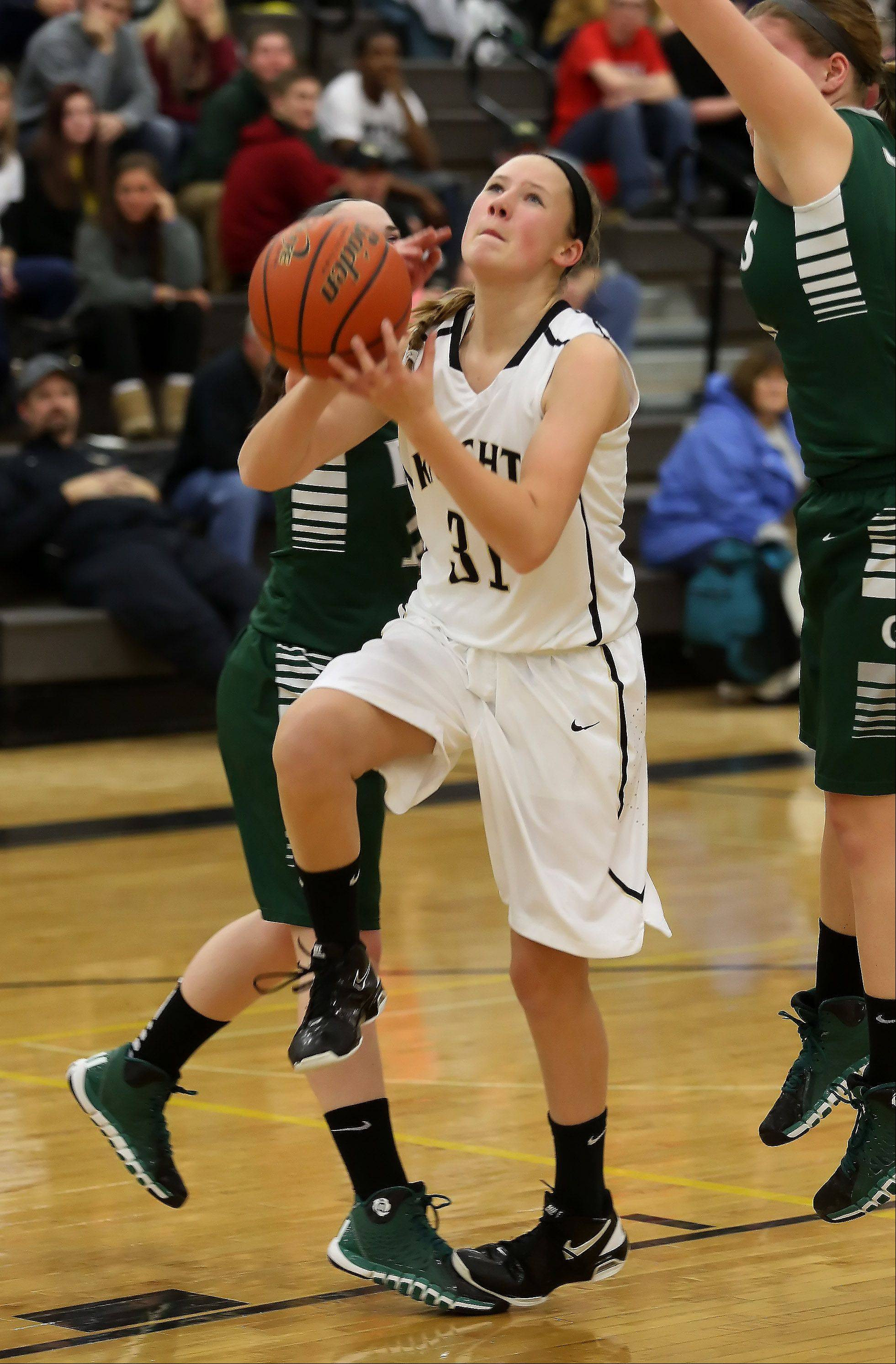 Grayslake North guard Kayla Hartigan is fouled as she goes up for a layup against Grayslake Central on Thursday at Grayslake North.