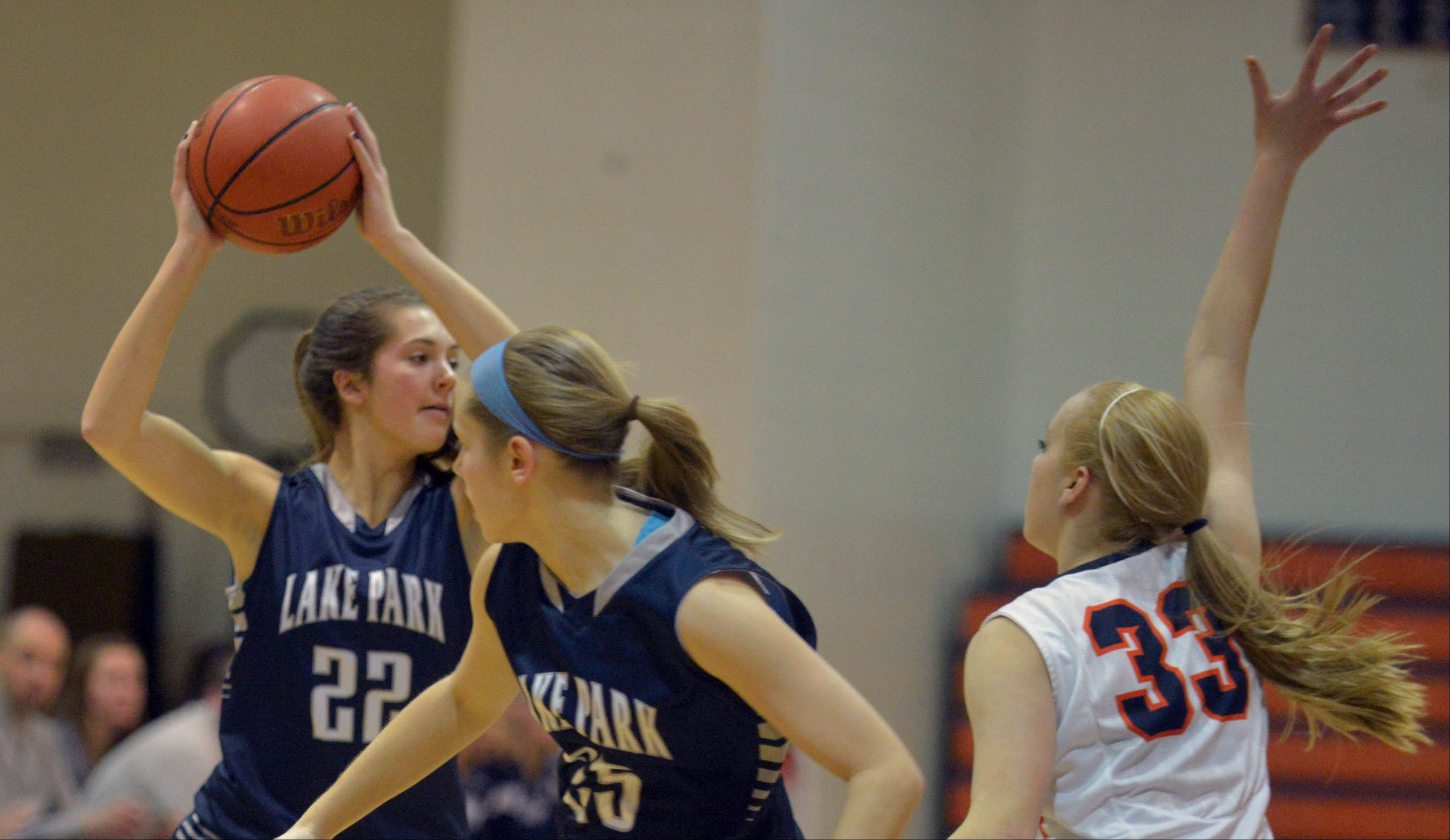 Alexis Pall of Lake Park looks for an open teammate while her fellow player Abbie Zastawny moves around Katie Cores of Naperville North.