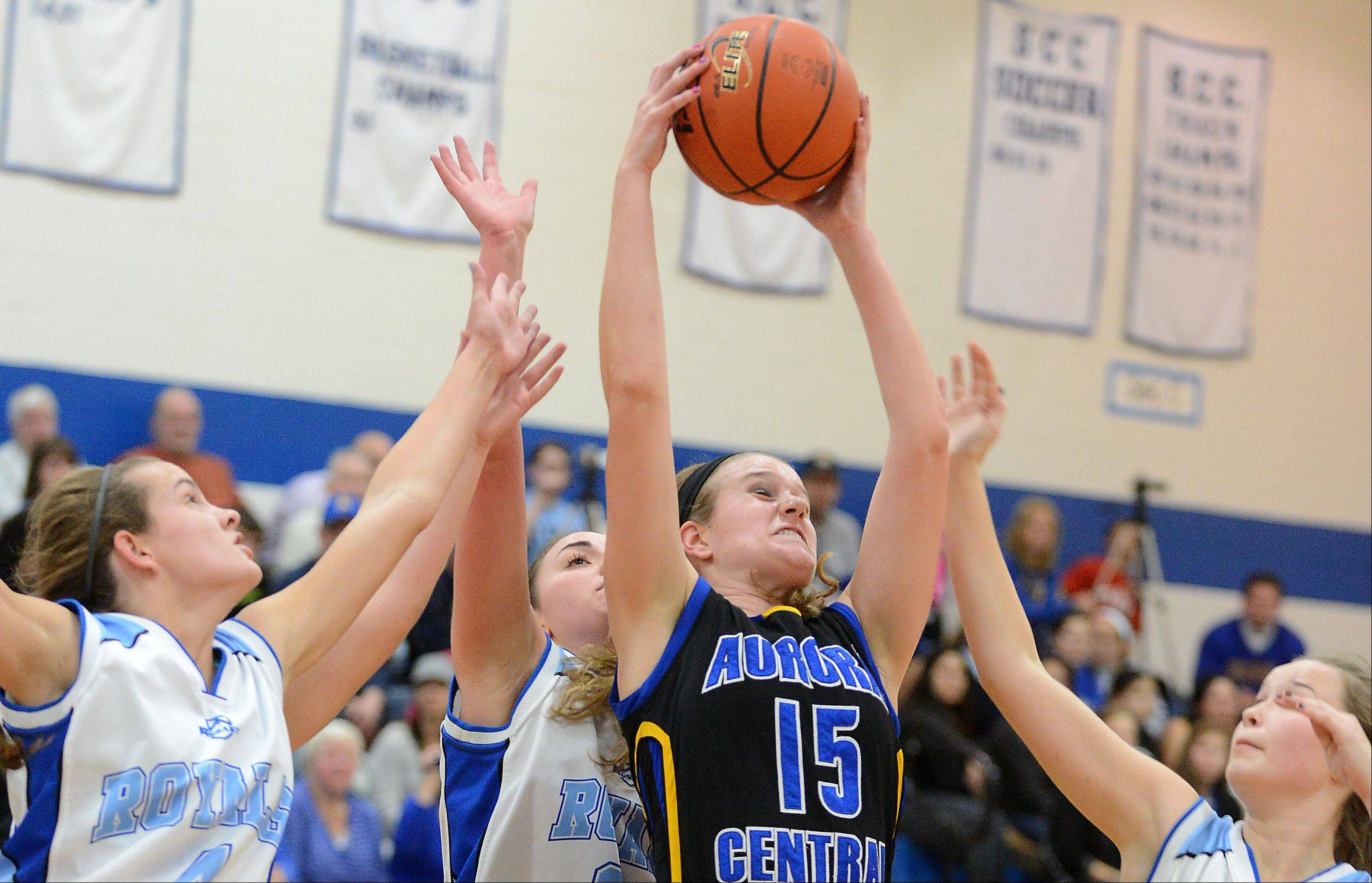 Aurora Central Catholic's Natalie Droeske pulls down a rebound while surrounded by Rosary players.