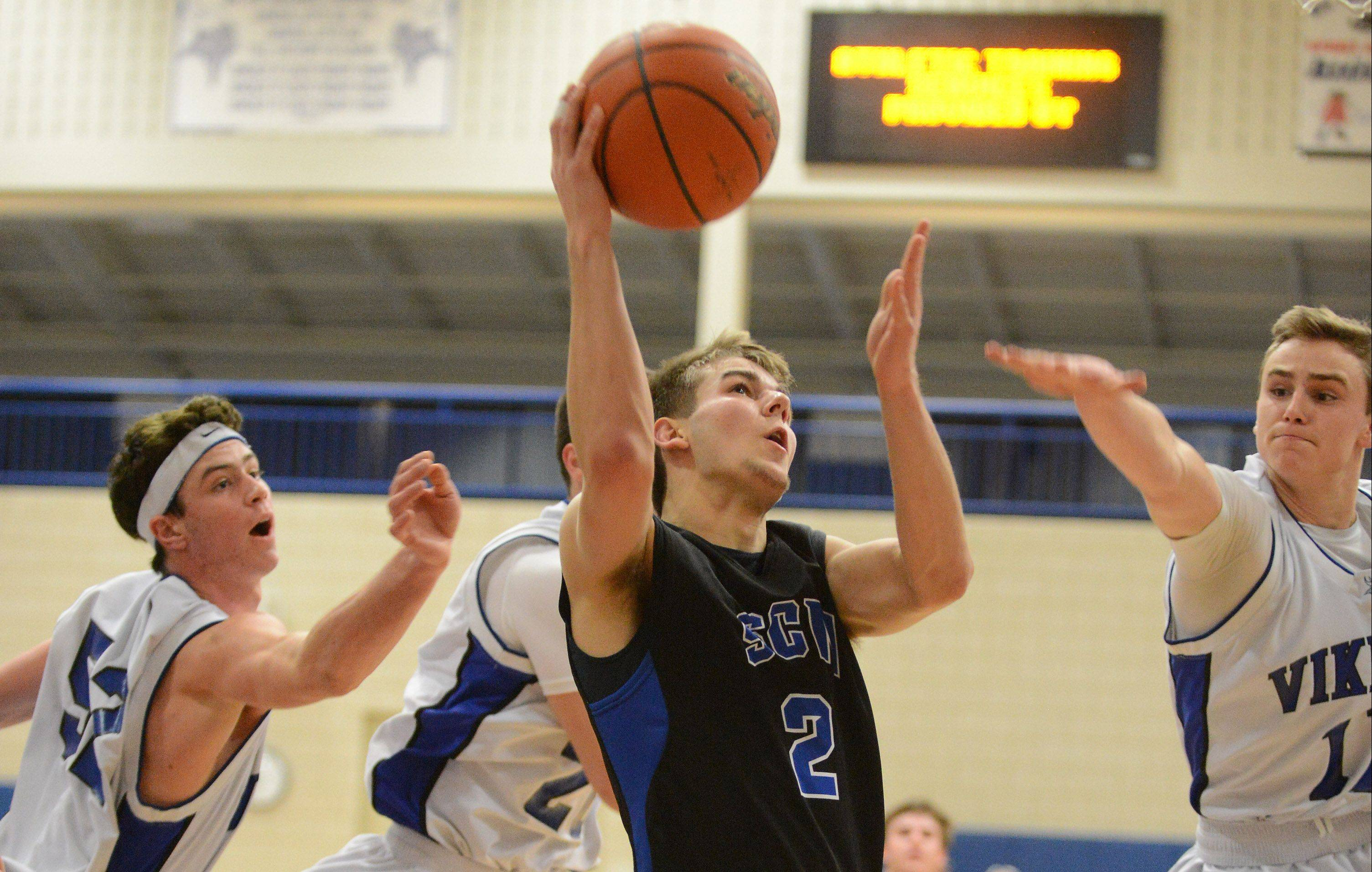 St. Charles North's Jake Ludwig (2) splits a trio of Geneva defenders to get a shot up during Friday's game in Geneva.