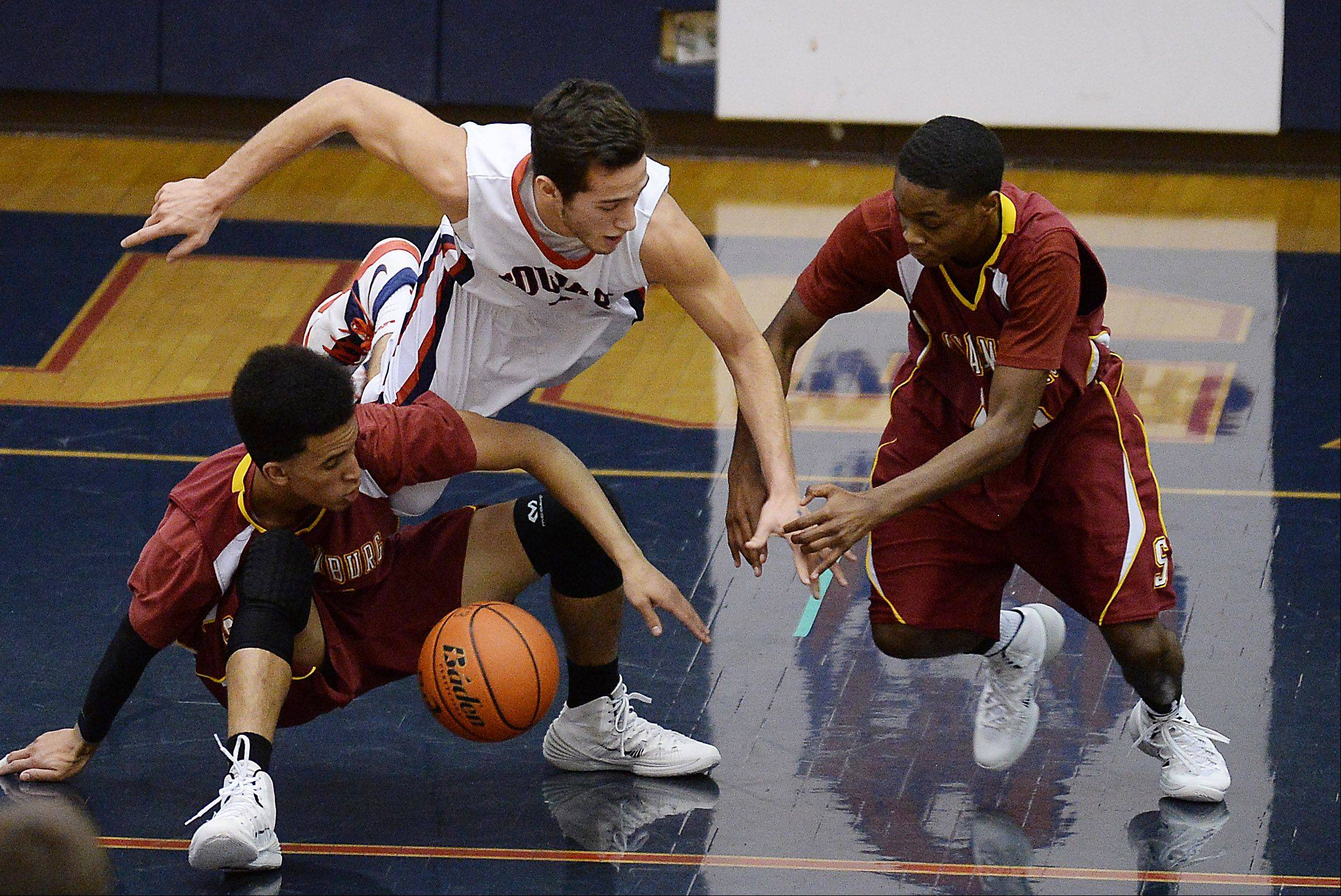 Conant's Joe Ranallo goes after a loose ball with Schaumburg's Brendan Parker and Marquis Woodard.
