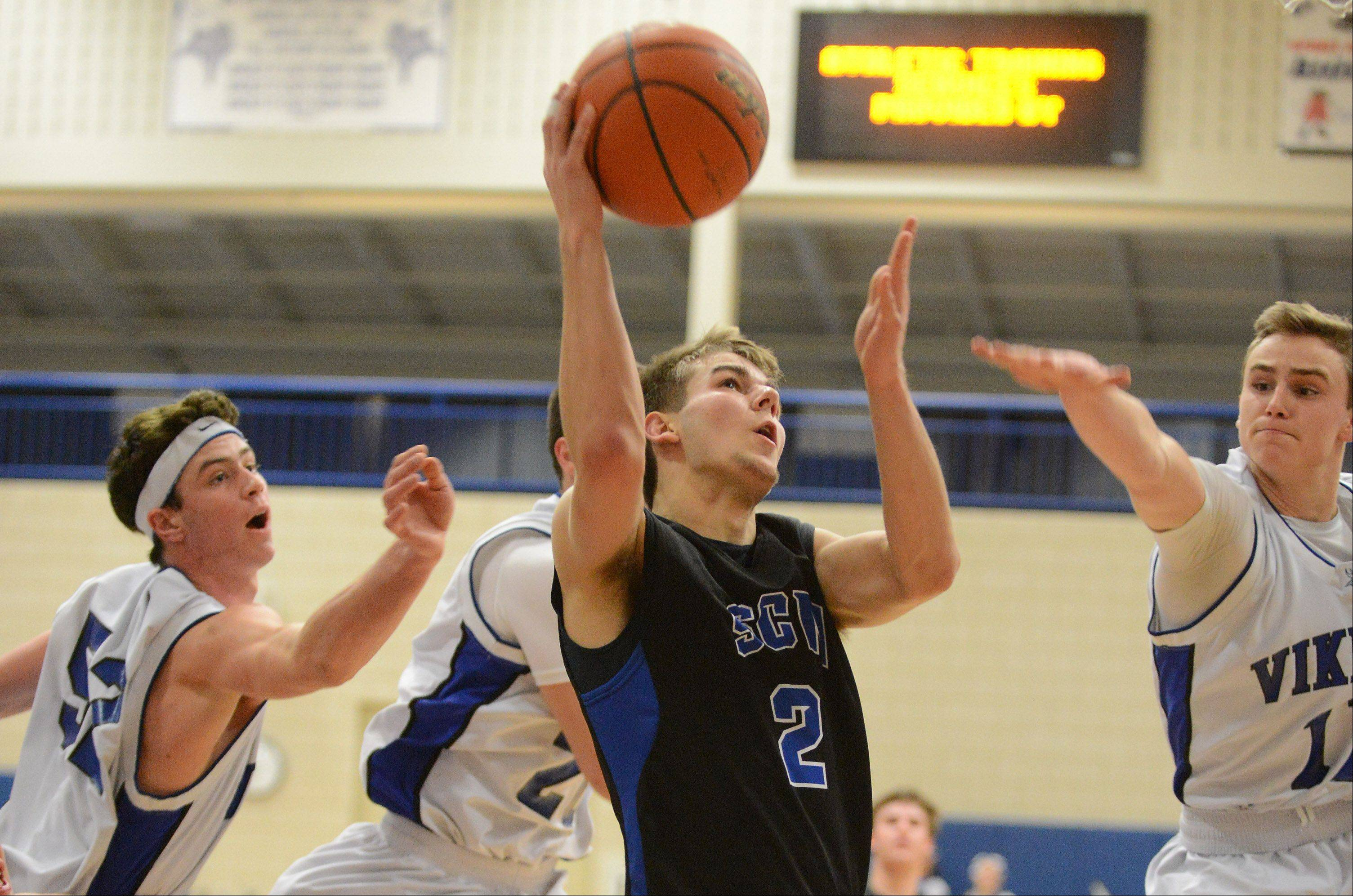 St. Charles North's Jake Ludwig splits a trio of Geneva defenders.