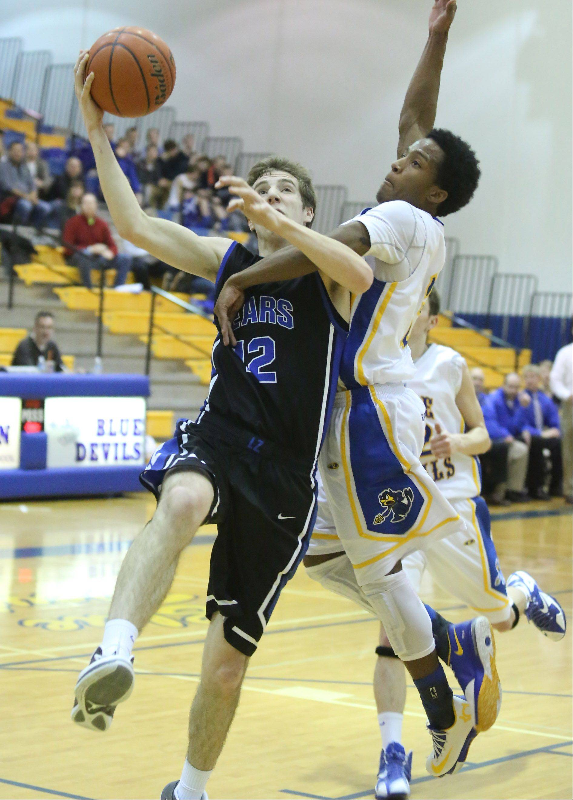 Warren defender Eric Gillespie is called for a shooting foul against Lake Zurich forward Corey Helgeson on a breakaway to the basket.