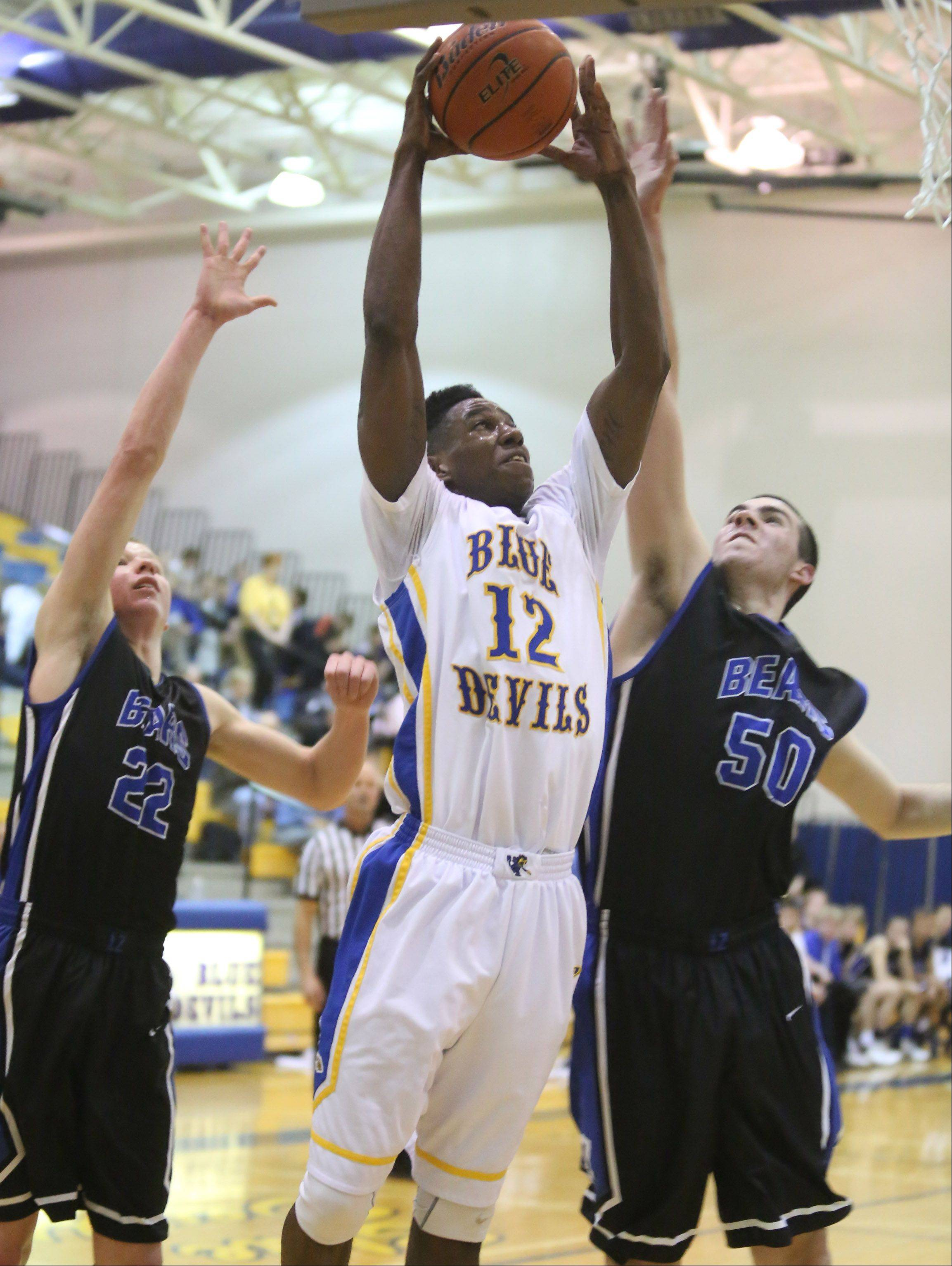 Warren forward Gregory Swane puts the ball up, splitting Lake Zurich defenders Brad Kruse, left, and Will McClaughry.