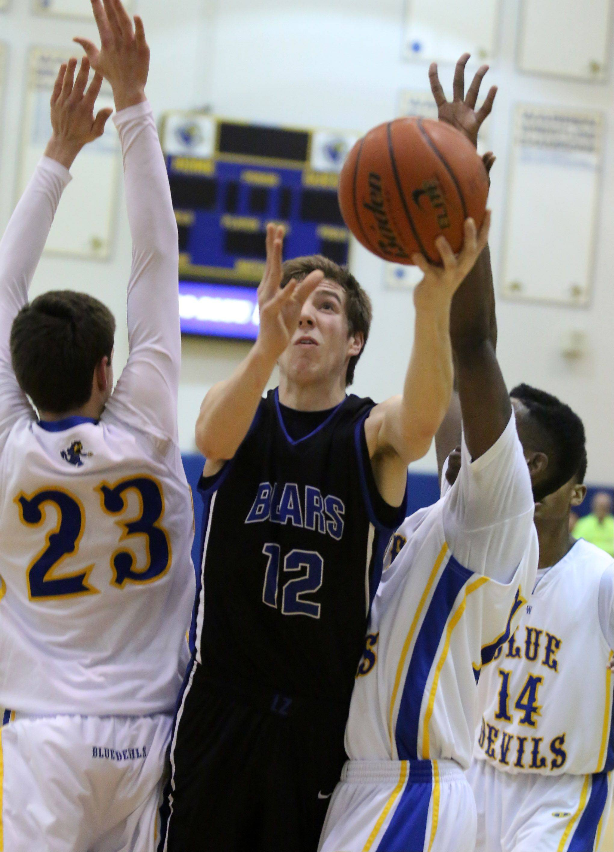 Lake Zurich forward Corey Helgeson shoots the ball around Warren defender Jovan Jokic, left.