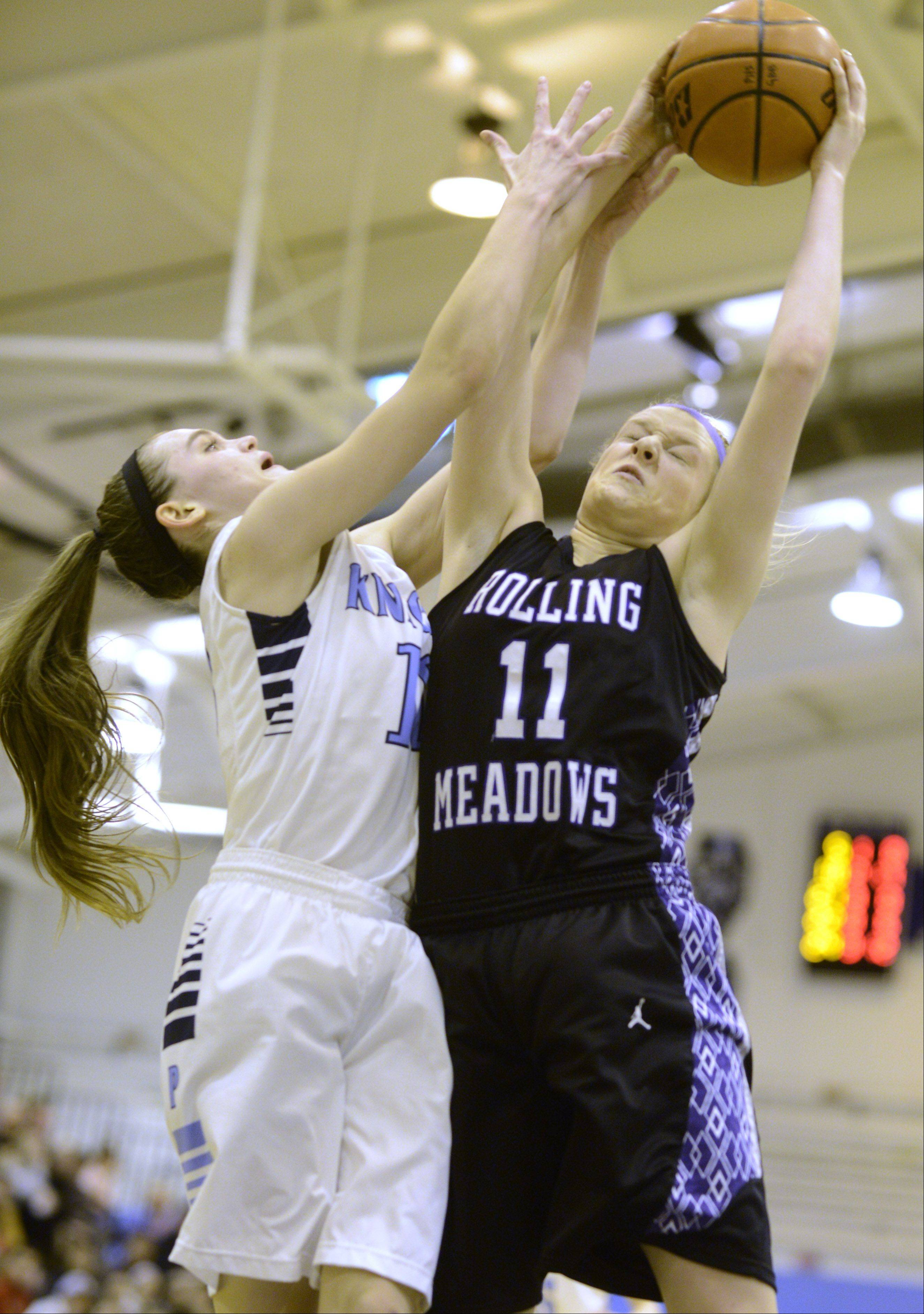 Prospect's Taylor Will, left, and Roling Meadows' Jenny Vliet leap for a rebound during Saturday's game.