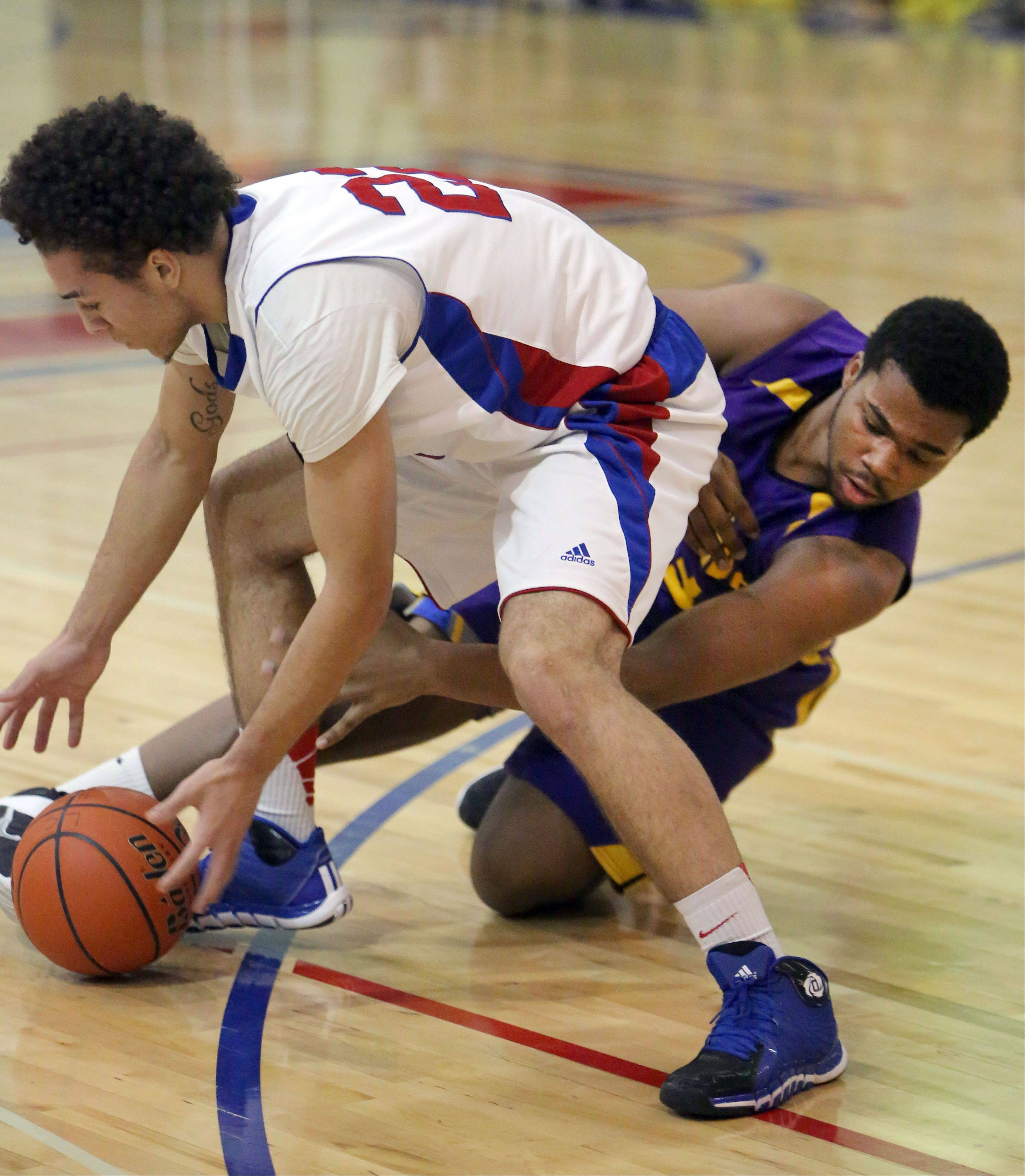 Steve Lundy/slundy@dailyherald.com Lakes' Tramone Hudson, left, and Wauconda's Dion Head scramble for a loose ball Tuesday night at Lakes.