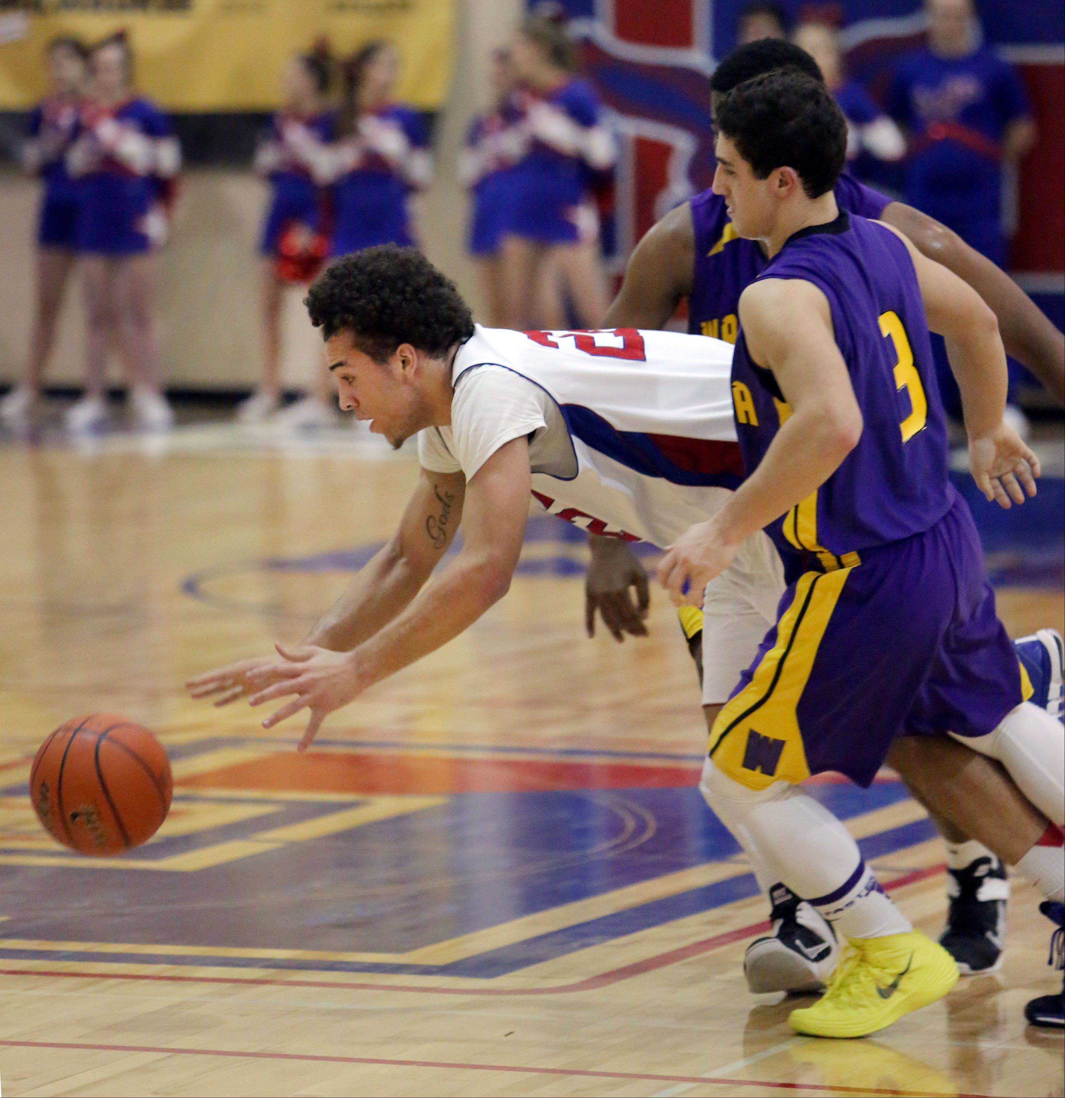 Lakes' Tramone Hudson dives for a loose ball as Wauconda's Joey Lovelle defends on Tuesday night at Lakes.