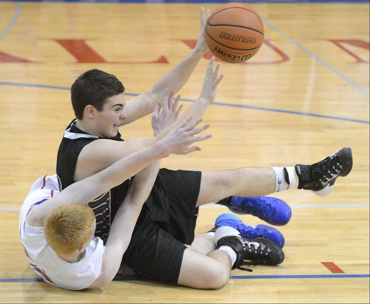 Kaneland's Connor Fedderly passes the ball while tumbling down with Marmion Academy's Matt Fletcher in the fourth quarter on Tuesday, January 14.