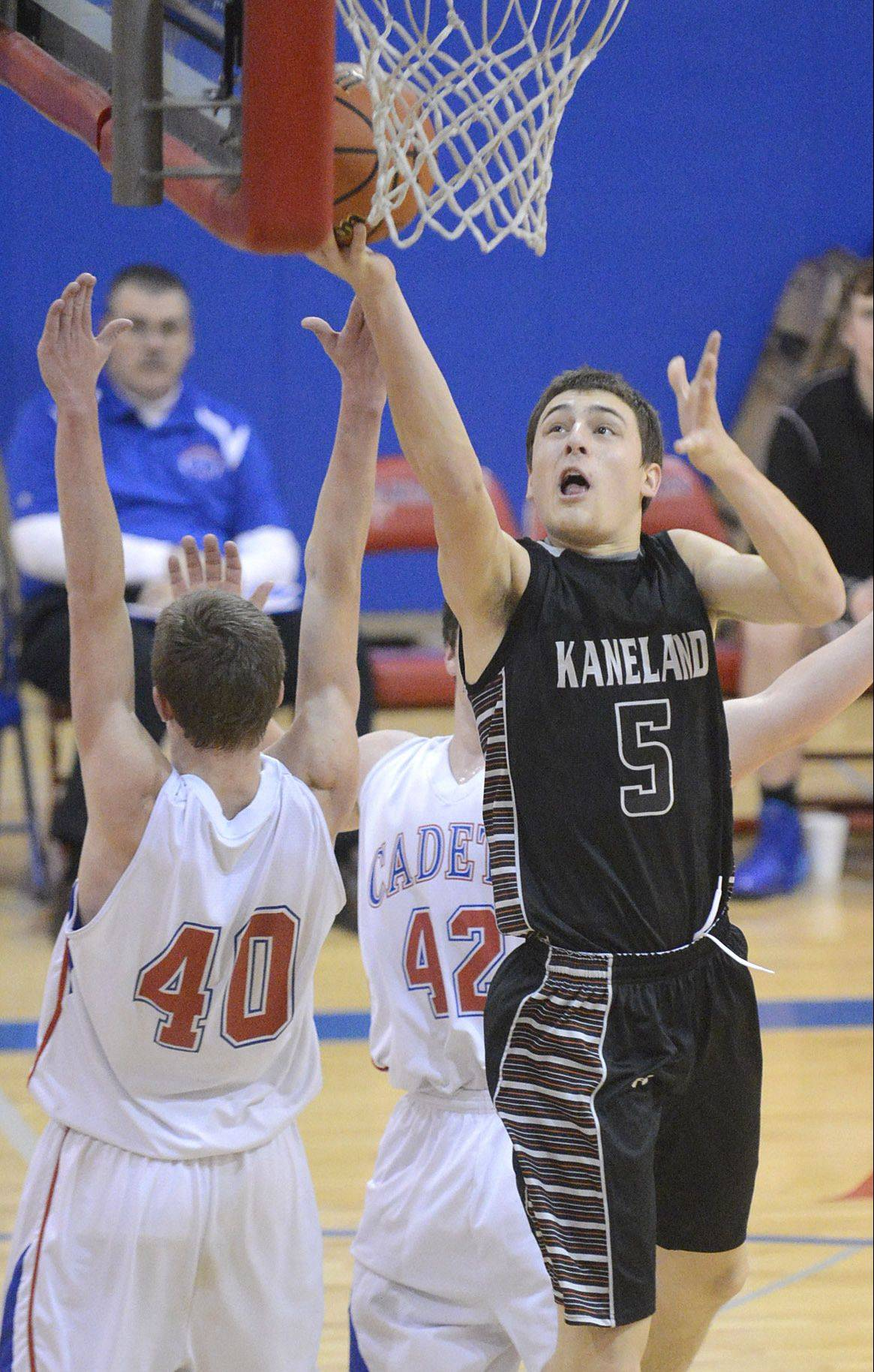 Kaneland's John Pruett lays in 2 of his 16 points against Marmion's Tyler Maryanski on Tuesday.