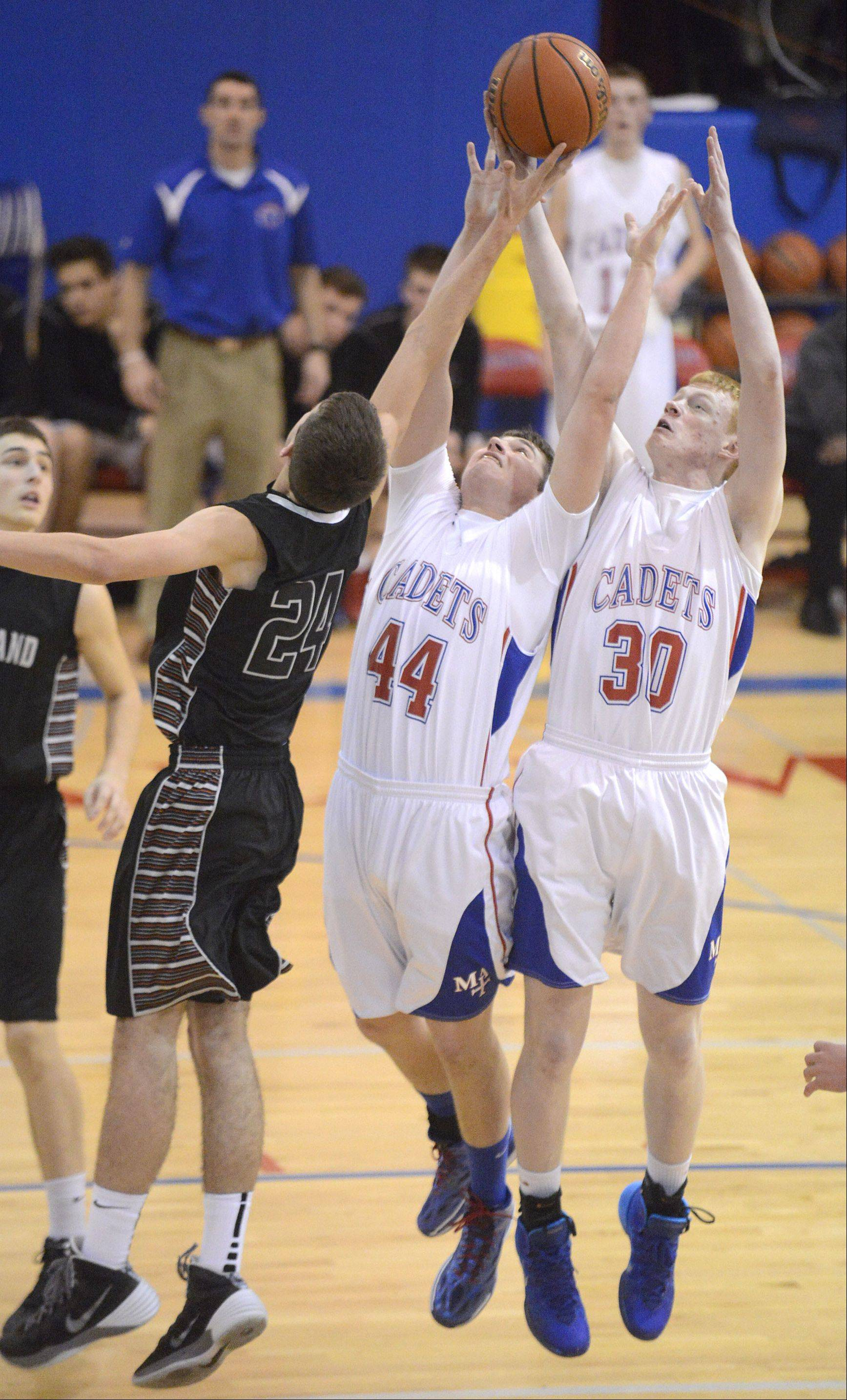 Kaneland's Ryan David leaps for a Knights rebound with Marmion Academy's Danny Bicknell (44) and Matt Fletcher (30) in the second quarter on Tuesday, January 14.