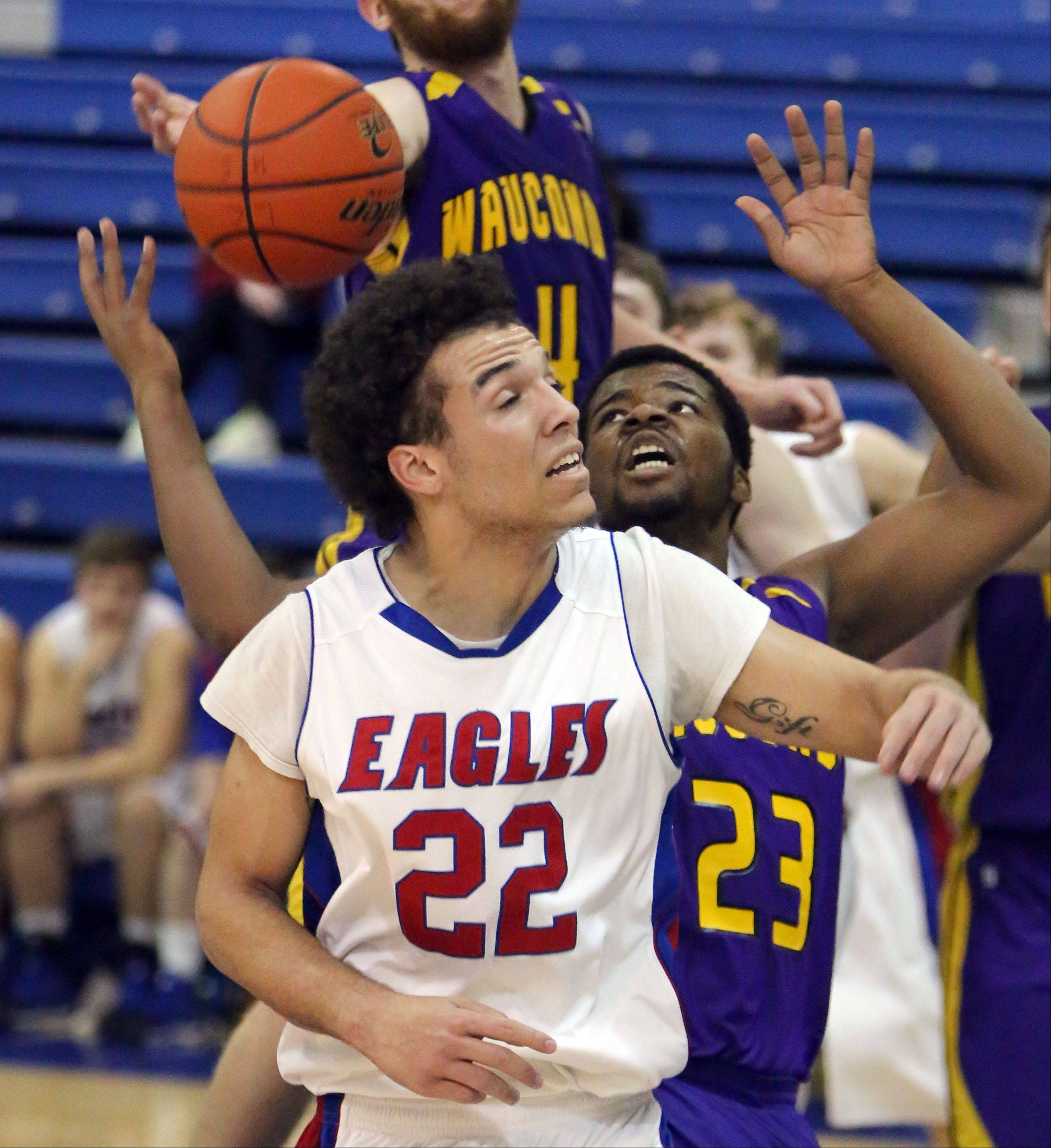 Lakes' Tramone Hudson, left, and Wauconda's Dion Head try to track down a rebound.