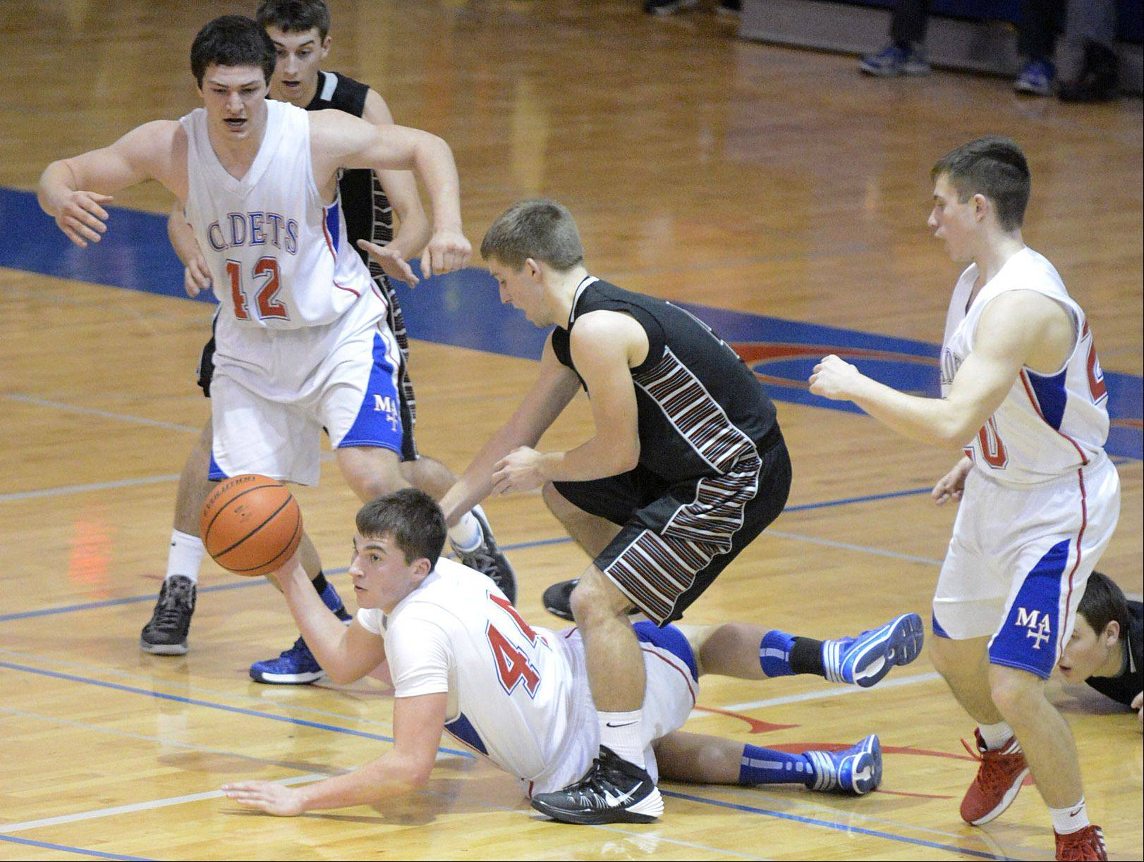 Marmion Academy's Danny Bicknell manages a pass while falling ahead of Kaneland's Drew David in the second quarter.