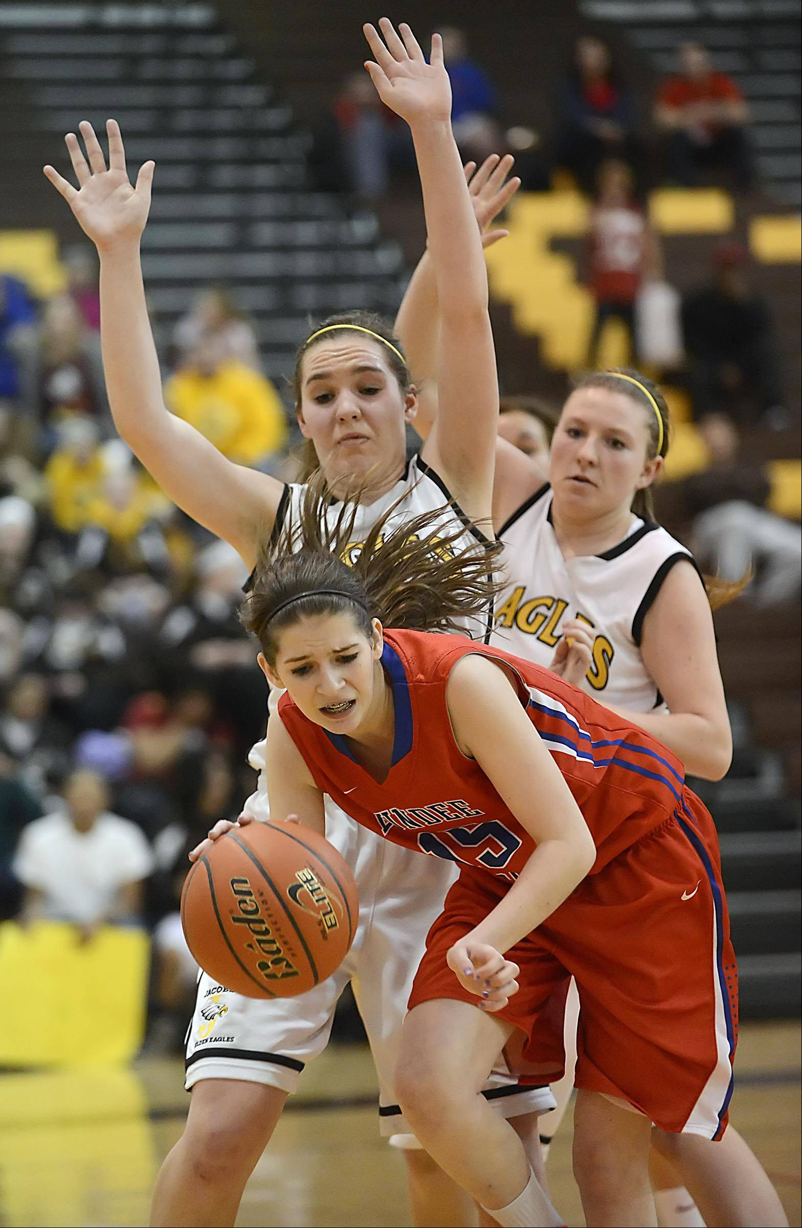 Dundee-Crown's Melissa Barker is turned away from the basket by Jacobs' Maggie Grady and Teaghan Richman, right.