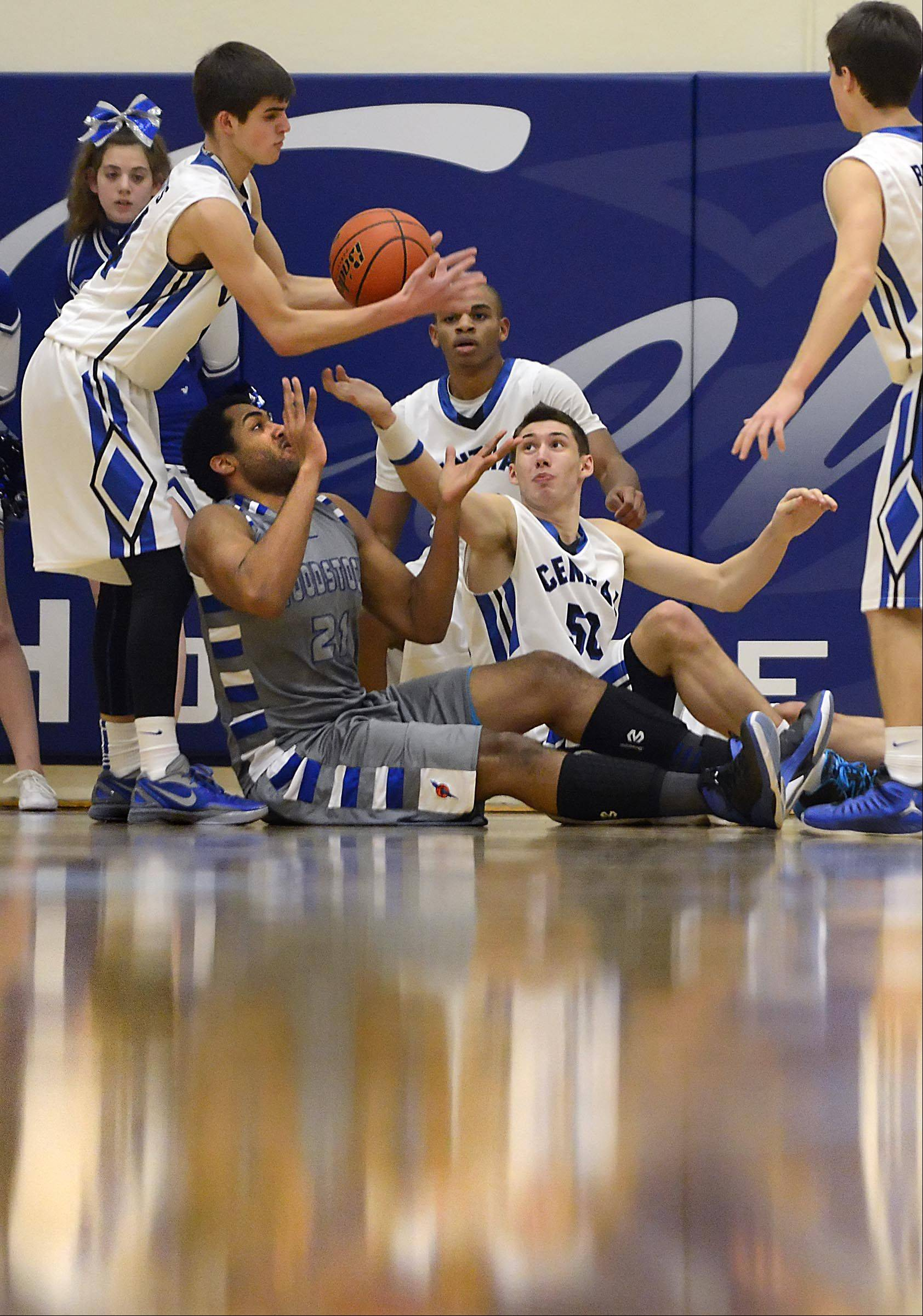 Burlington Central's Brett Rau grabs a loose ball as teammate Duncan Ozburn and Woodstock's Damian Stoneking reach from the floor.