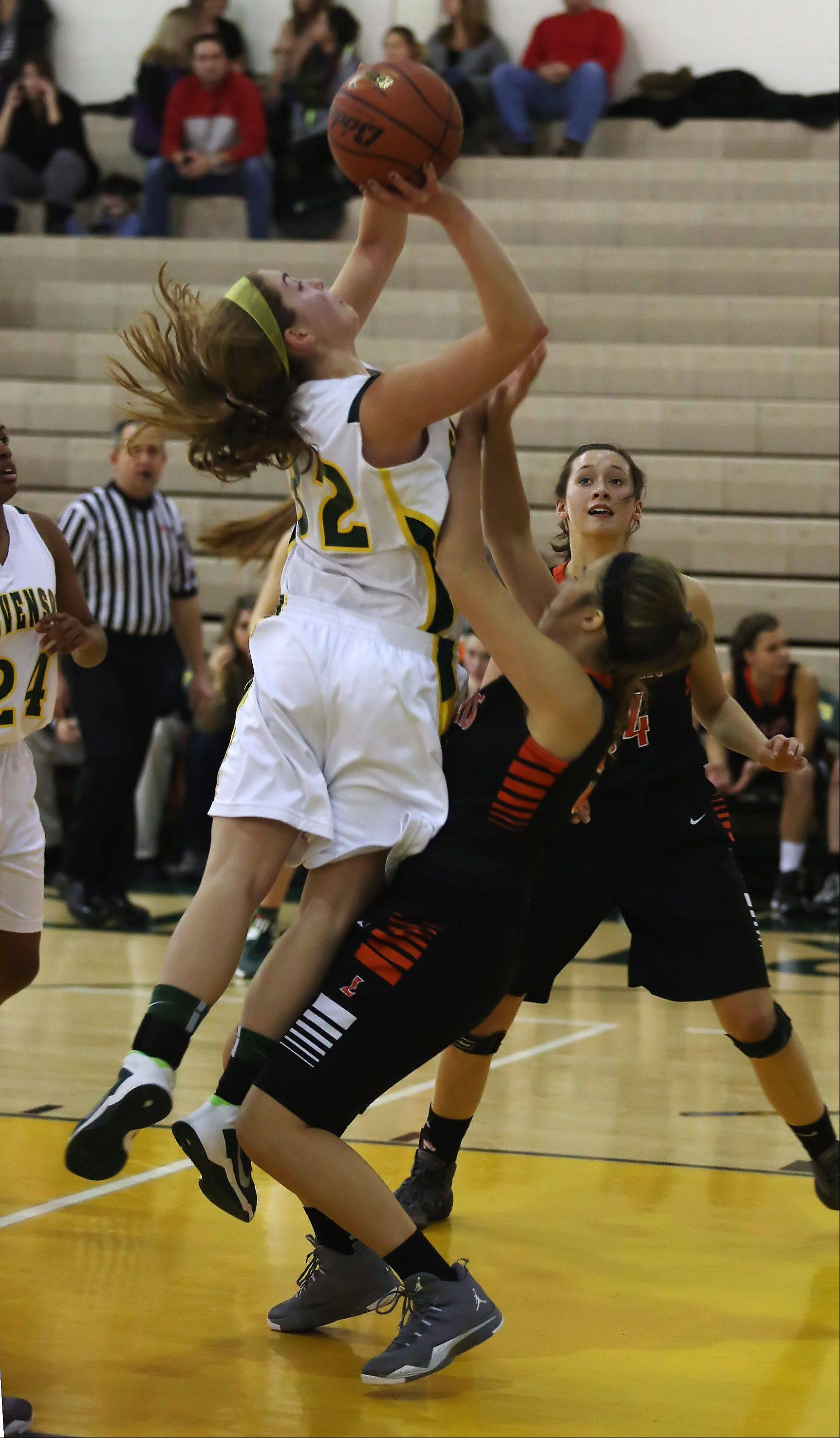 Libertyville forward Tara Eyre, right, takes a charge from Stevenson forward Sophia Way on Thursday at Stevenson.