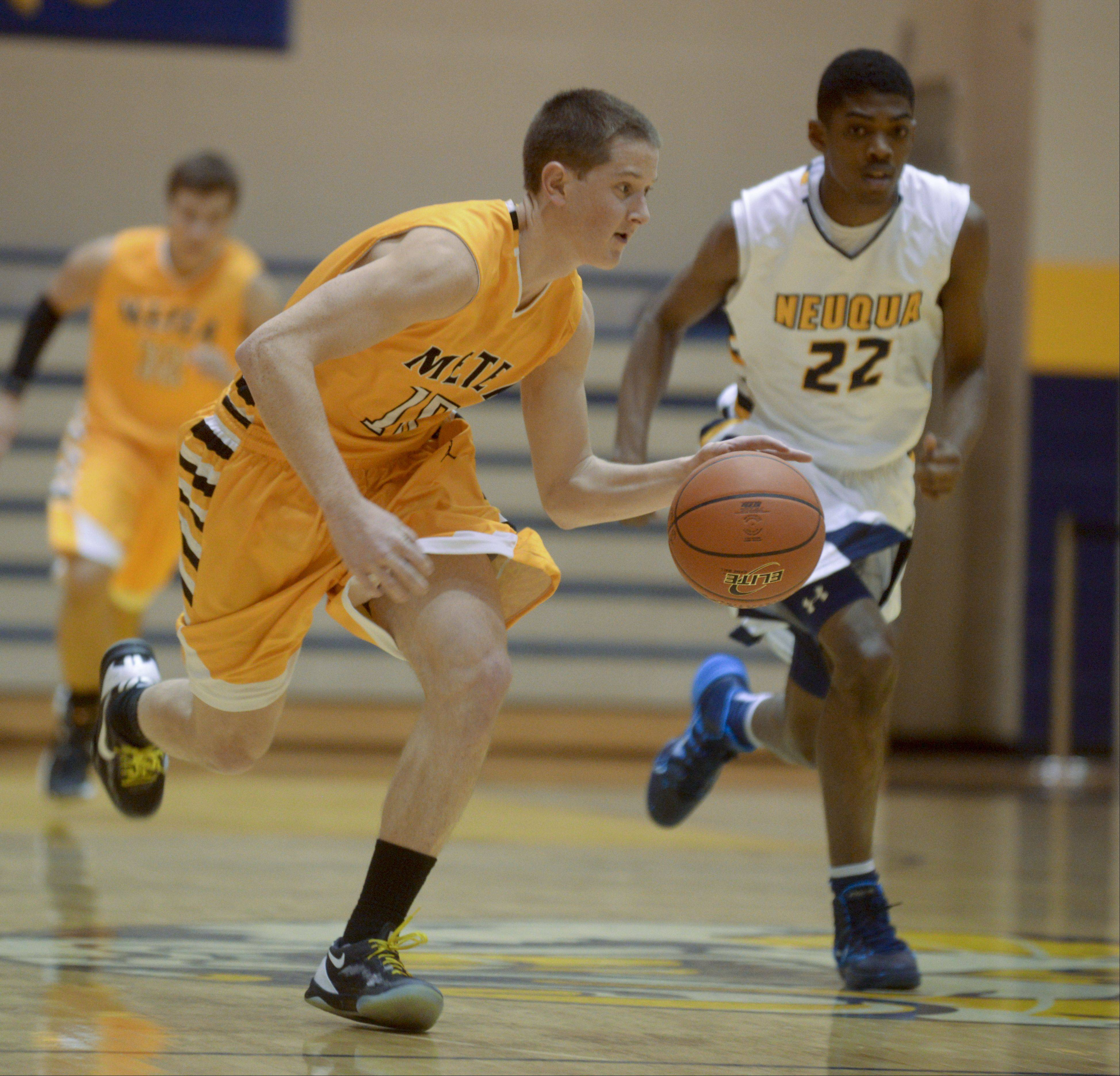 Justin Kuehn of Metea Valley drives with the ball as Elijah Robertson of Neuqua Valley follows close behind.