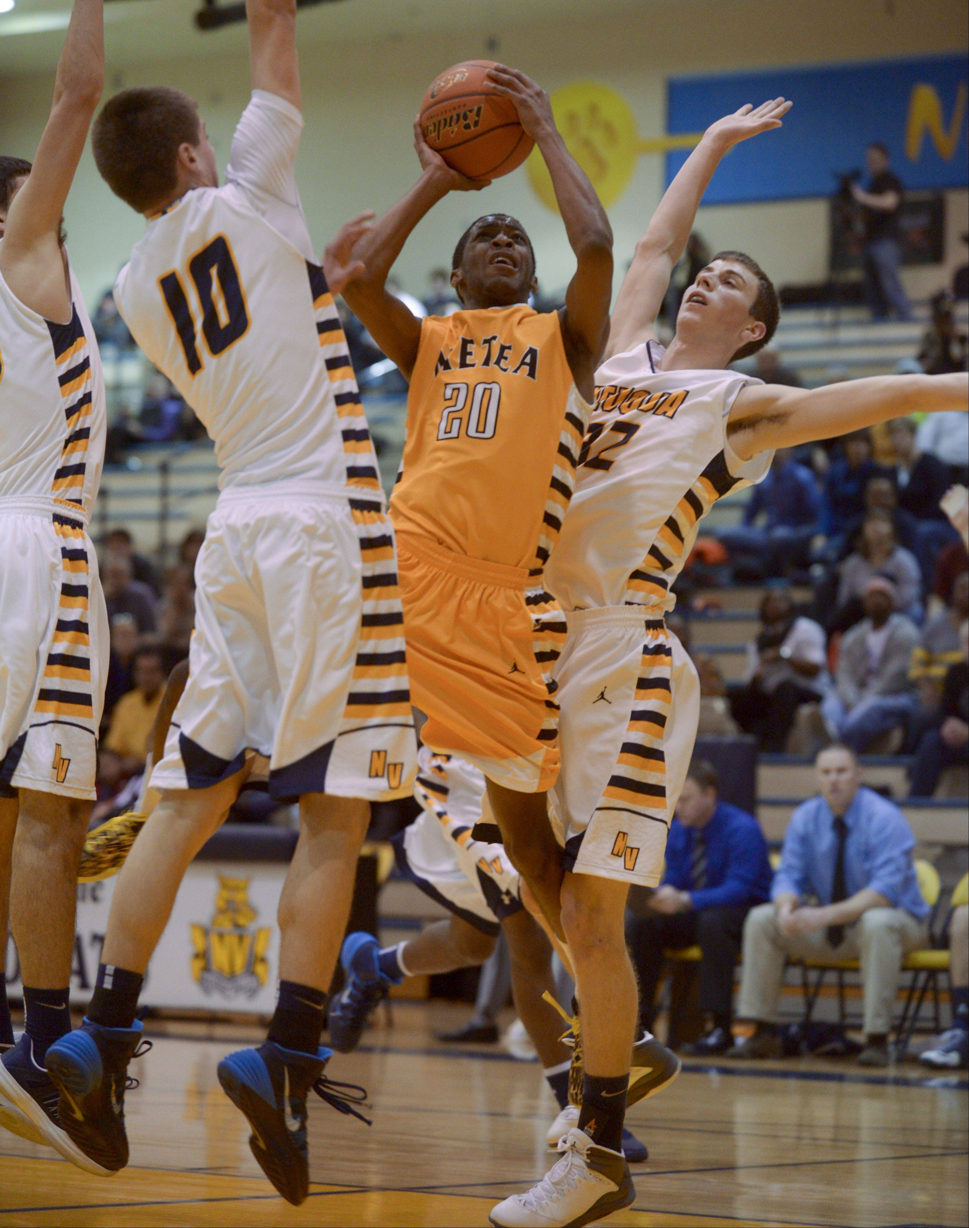 Marquell Oliver of Metea Valley goes up for a shot between Jacob Eminger and Connor Raridon of Neuqua Valley .